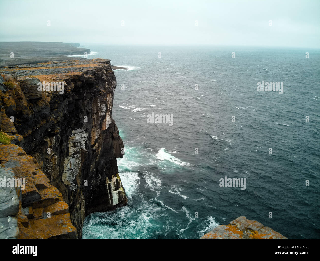 Aran Island - Inish More west side cliffs in cold rainy weather. Weaves hitting the rock again and again. - Stock Image