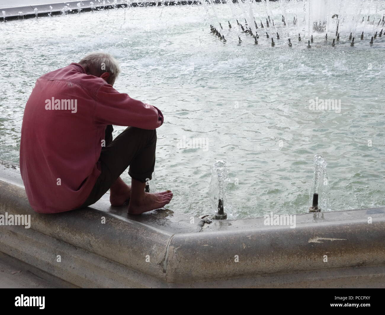 old man feeling hot and uncomfortable in the heatwave tries to keep cool by putting his feet in the cool fountain water - Stock Image