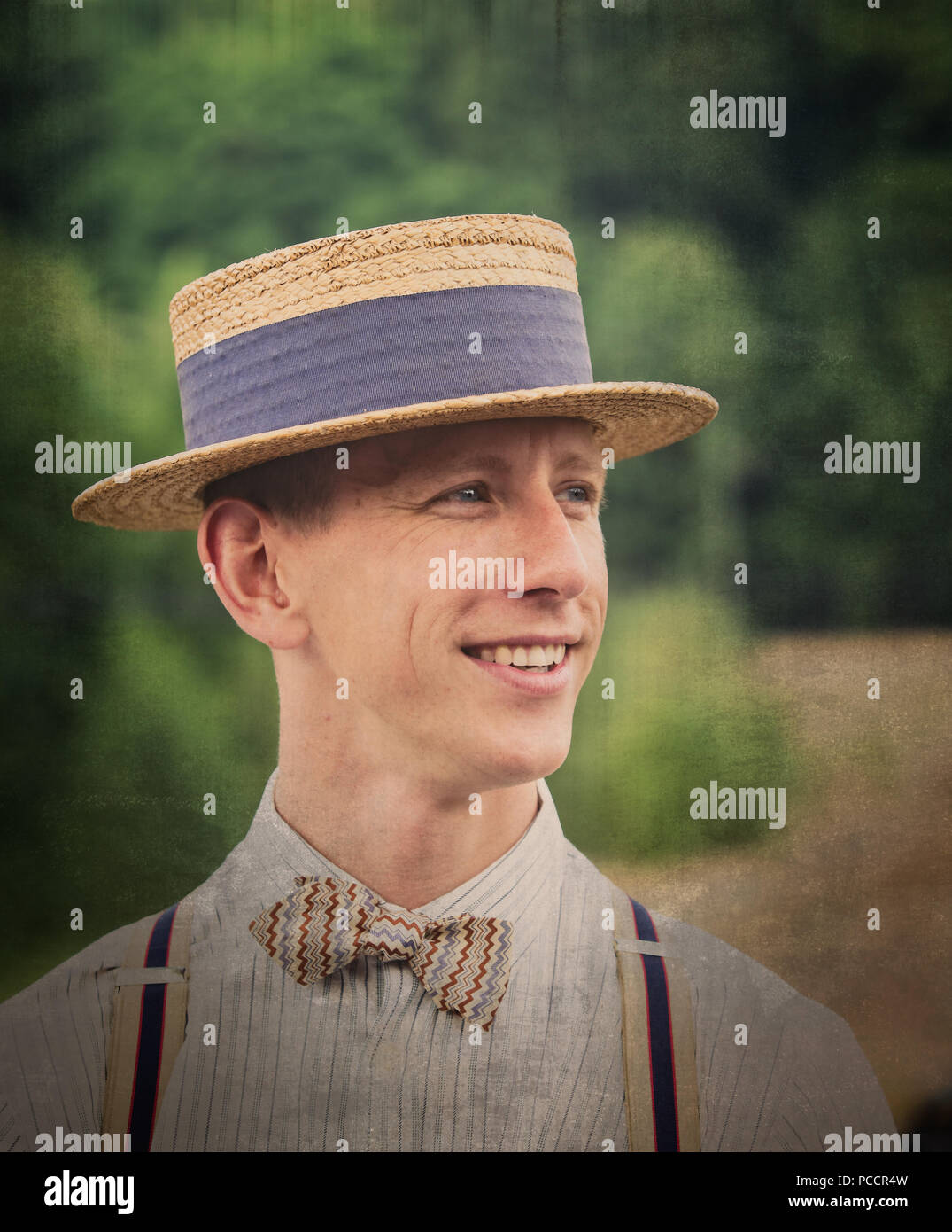 Close-up portrait of stylish young man in 1940's costume looking dapper in straw boater, bow tie & braces, at Black Country Museum 1940's WWII event. - Stock Image