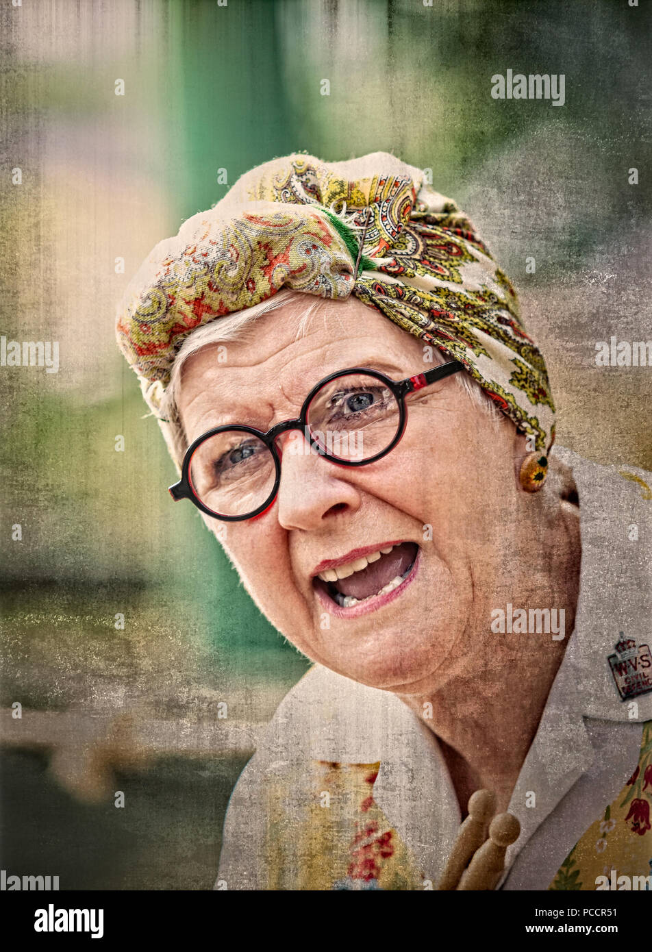 Close-up portrait of woman in 1940's costume dressed as cleaning lady (charlady) wearing head scarf & overalls, Black Country Museum 1940's event. - Stock Image