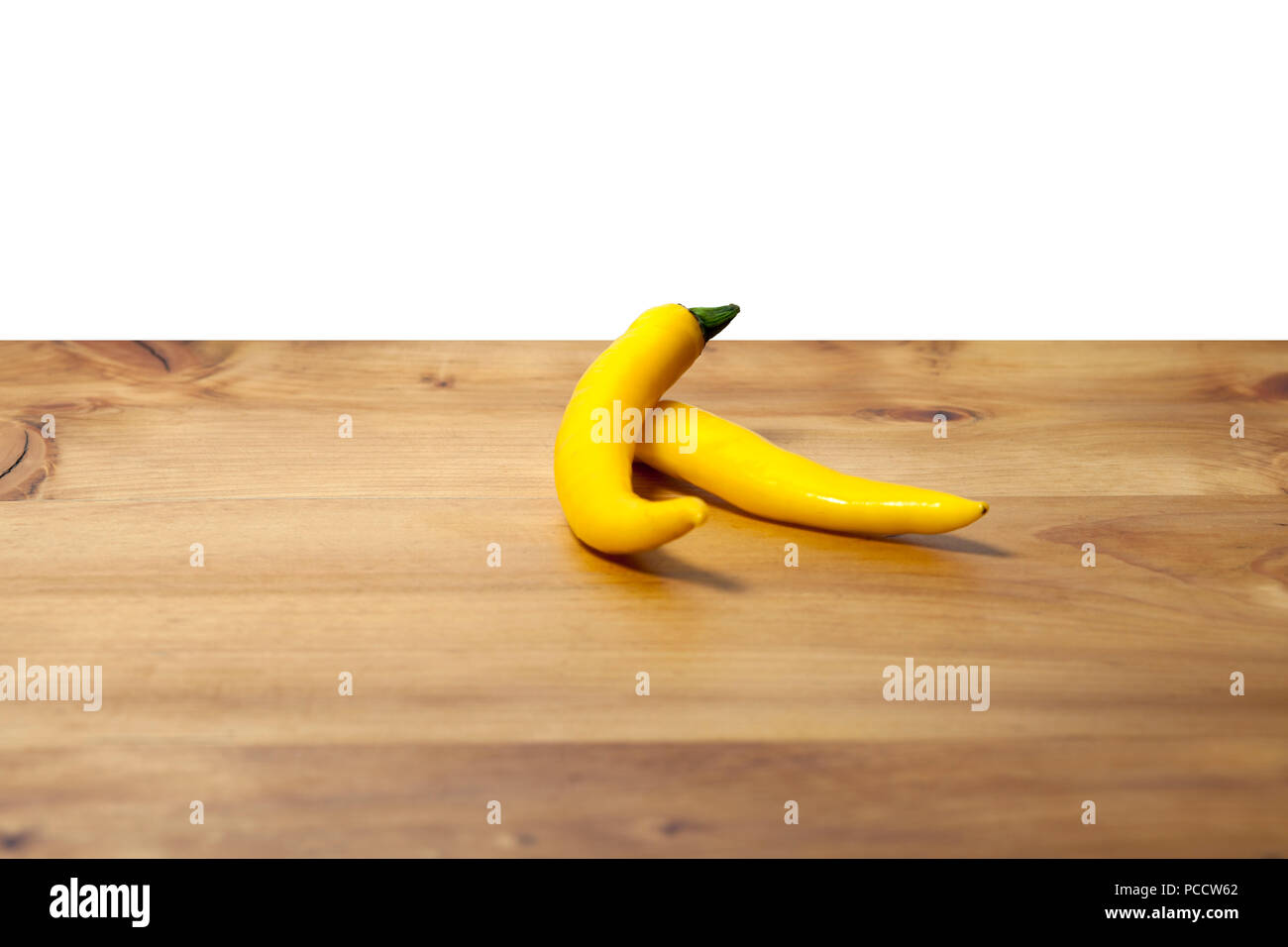 Two isolated yellow hot chilli peppers as ingredient of spice meal or salad on a wooden board with copyspace - Stock Image