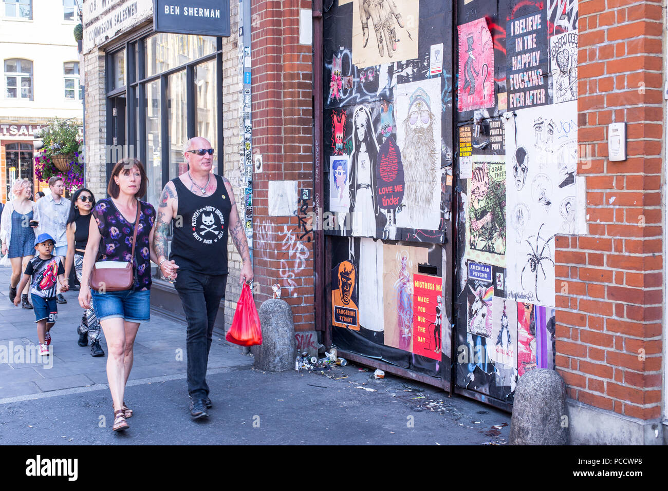 Male punk rock senior man holding hands with partner walking in front of wall covered in street art murals and posters in Commercial Street, in front  Stock Photo