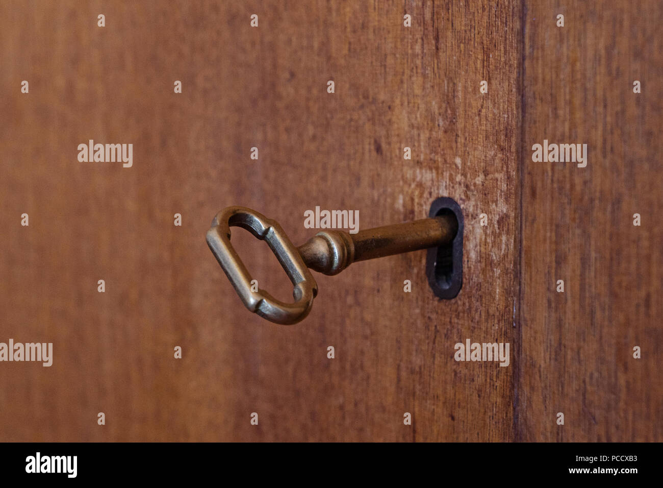 Old wooden cabinet with vintage key in keyhole, shallow depth of field selective focus, copy space Stock Photo