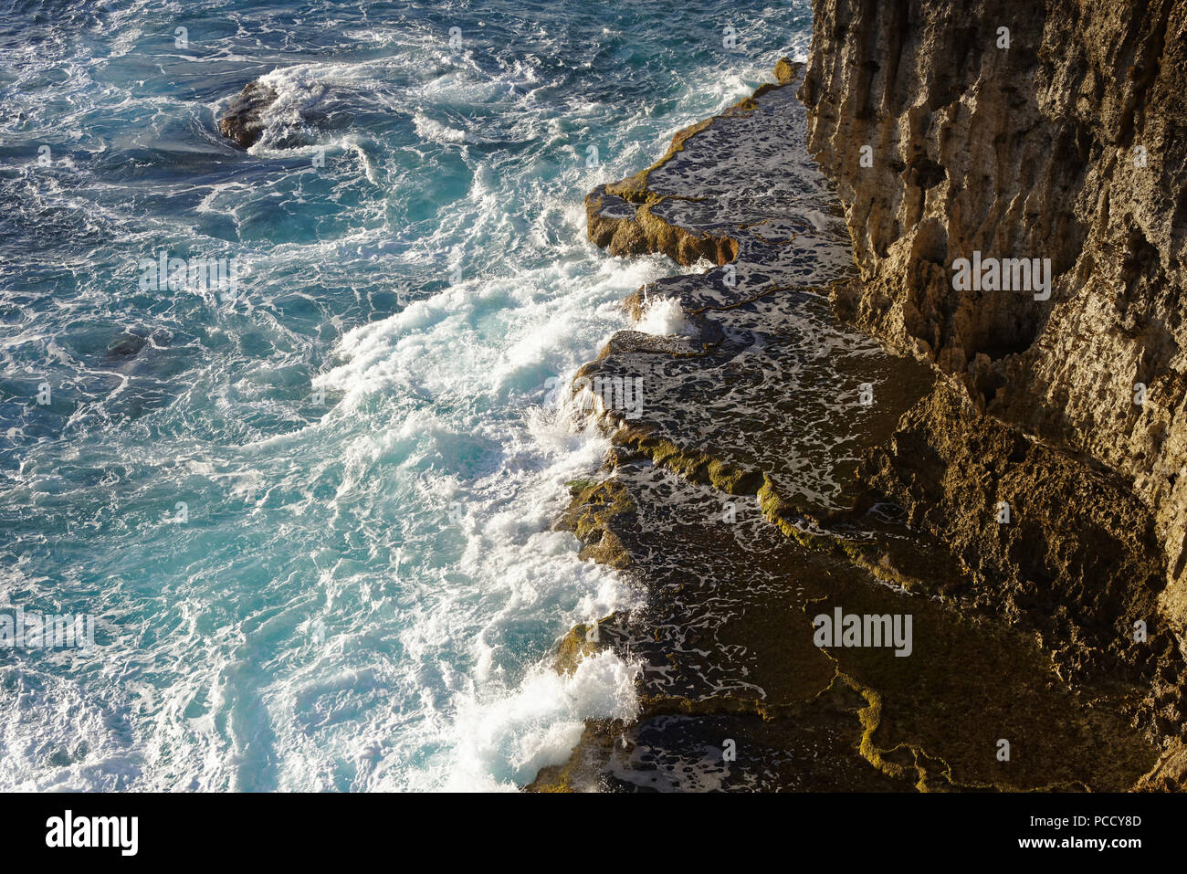 The sea crashes onto rocks at the bottom of a cliff in Tonga - Stock Image