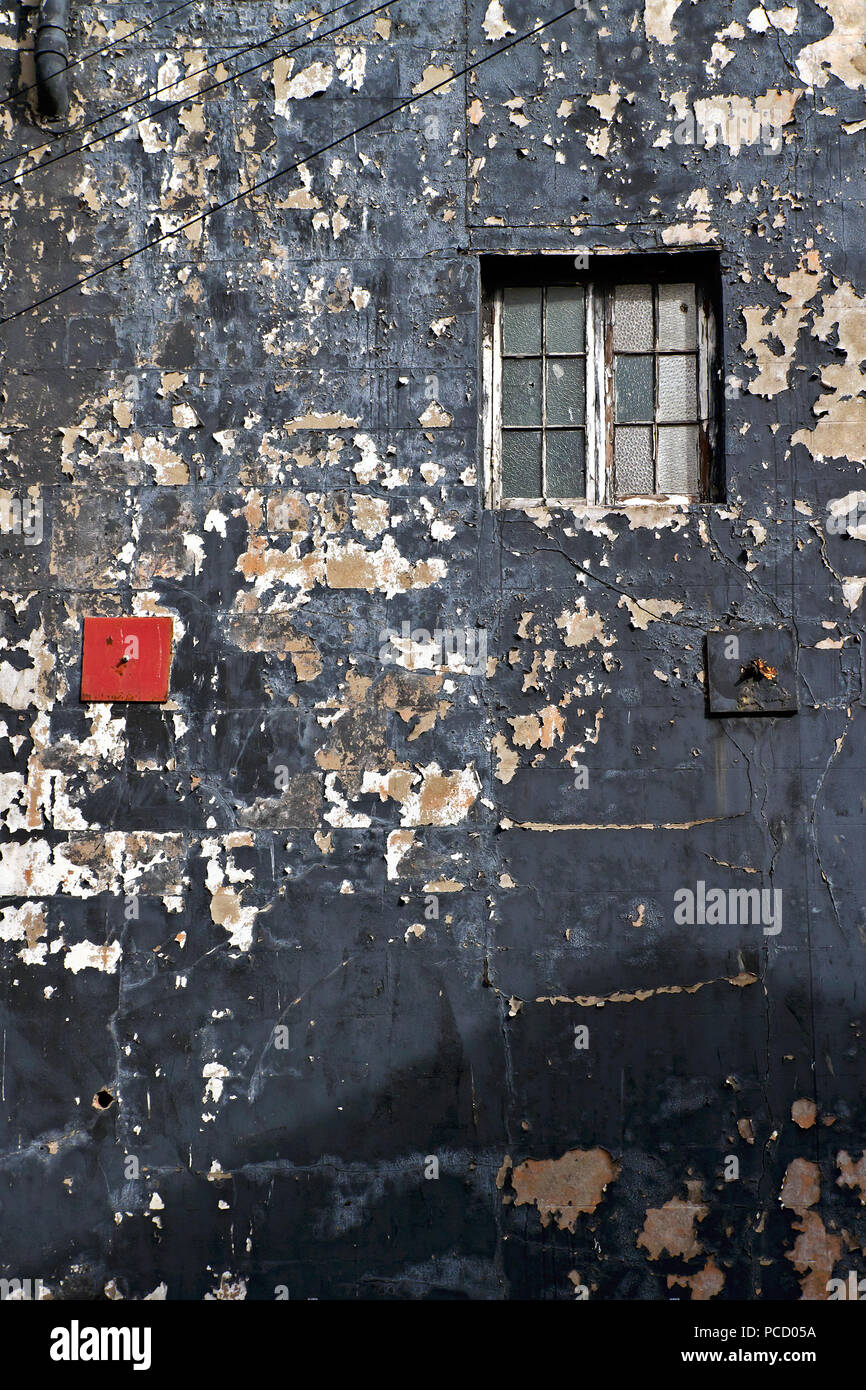 A bright red tie-bar plate contrasts vividly with its black neighbour and worn and decrepit surroundings on a shabby and weathered wall. - Stock Image