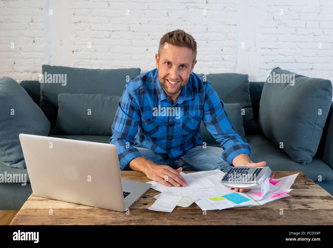 Young attractive american business man at home sitting on sofa with credit card and calculator accounting costs, charges, taxes and mortgage for payin - Stock Image