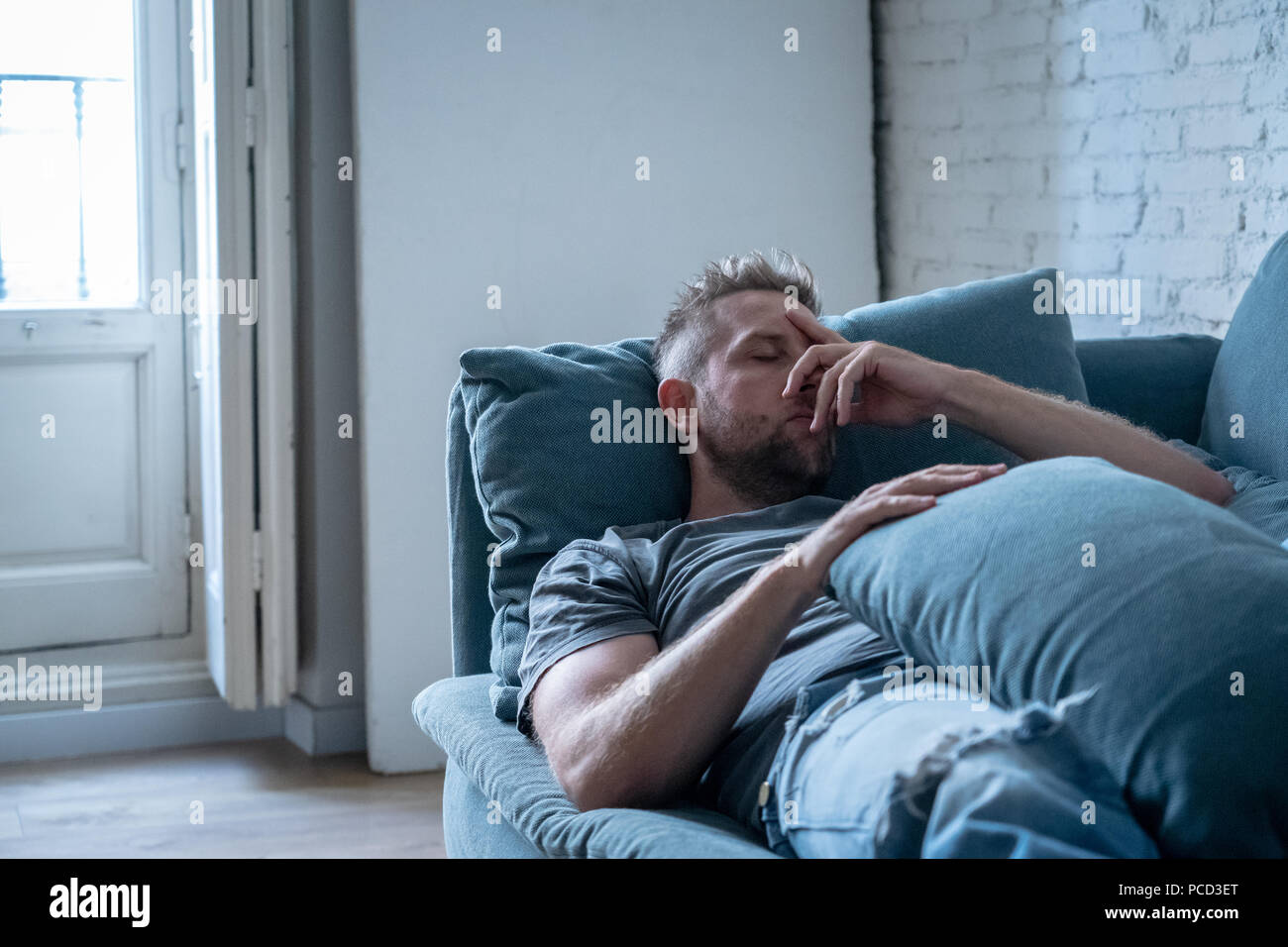 Unhappy depressed caucasian male sitting and lying in living room couch feeling desperate a lonely. In stressed from work, anxiety, heartbroken and de - Stock Image