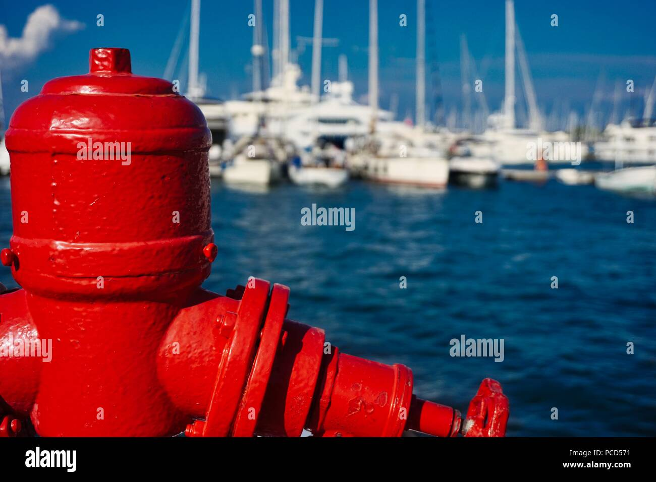 Red water hydrant on the quay of a yacht marina in the Greek Islands - Stock Image