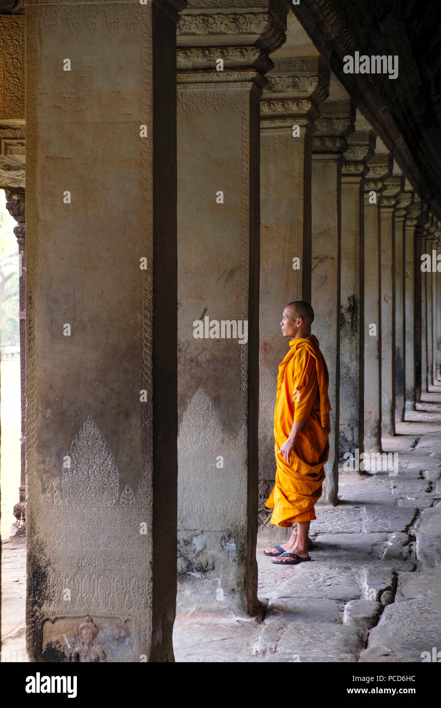 Buddhist monk in a colonnaded corridor in a temple in Angkor Wat, UNESCO World Heritage Site, Siem Reap, Cambodia, Indochina, Southeast Asia, Asia - Stock Image