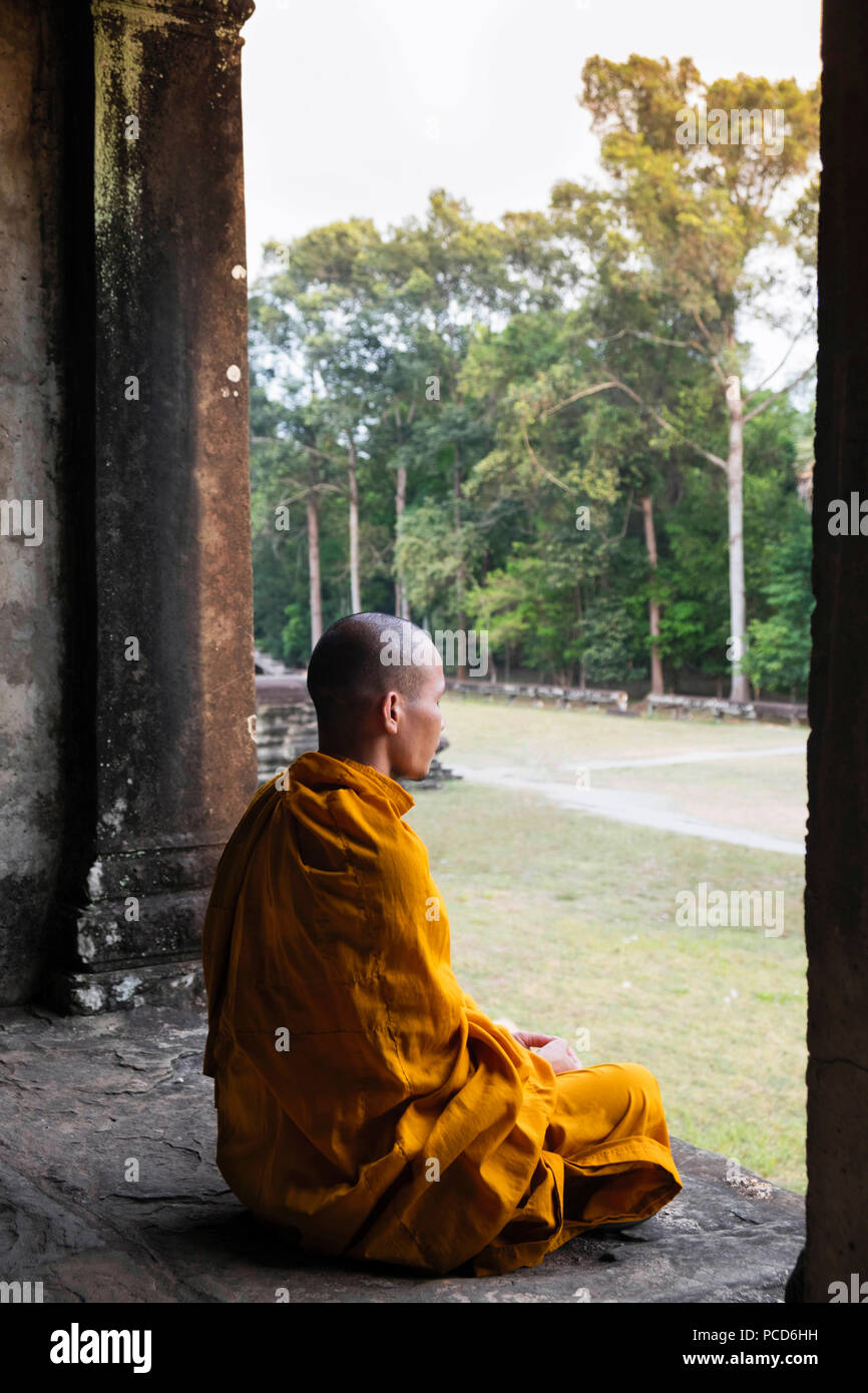 Buddhist monk sitting in a colonnaded corridor in a temple in Angkor Wat, UNESCO, Siem Reap, Cambodia, Indochina, Southeast Asia, Asia Stock Photo