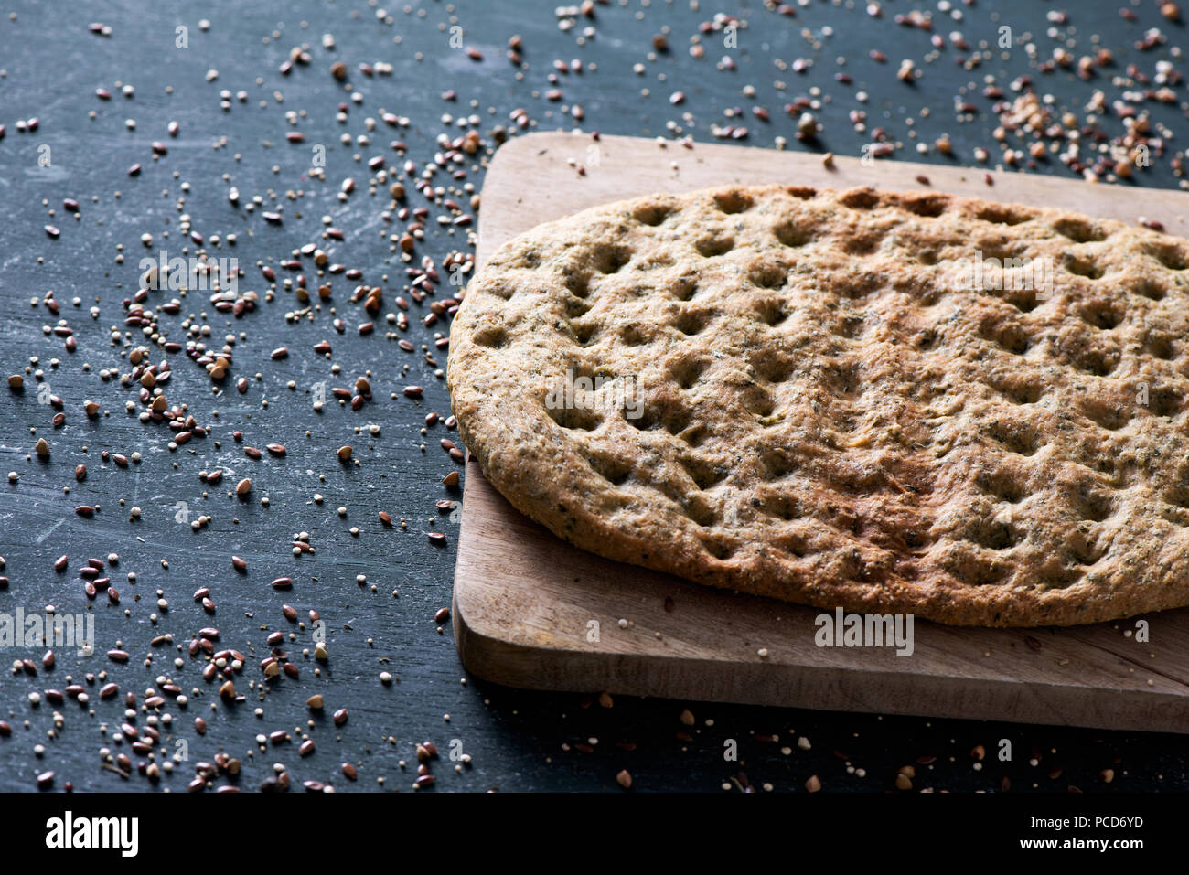 closeup of a kale flatbread on a chopping board, placed on a dark green rustic wooden table sprinkled with different spices - Stock Image