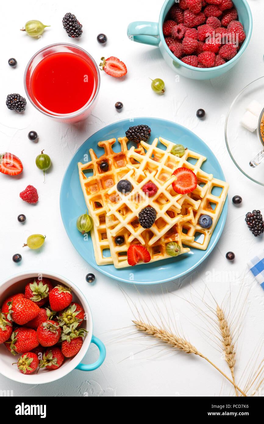 Photo of Viennese waffles,, coffee, raspberries, strawberries, gooseberries, cherries - Stock Image