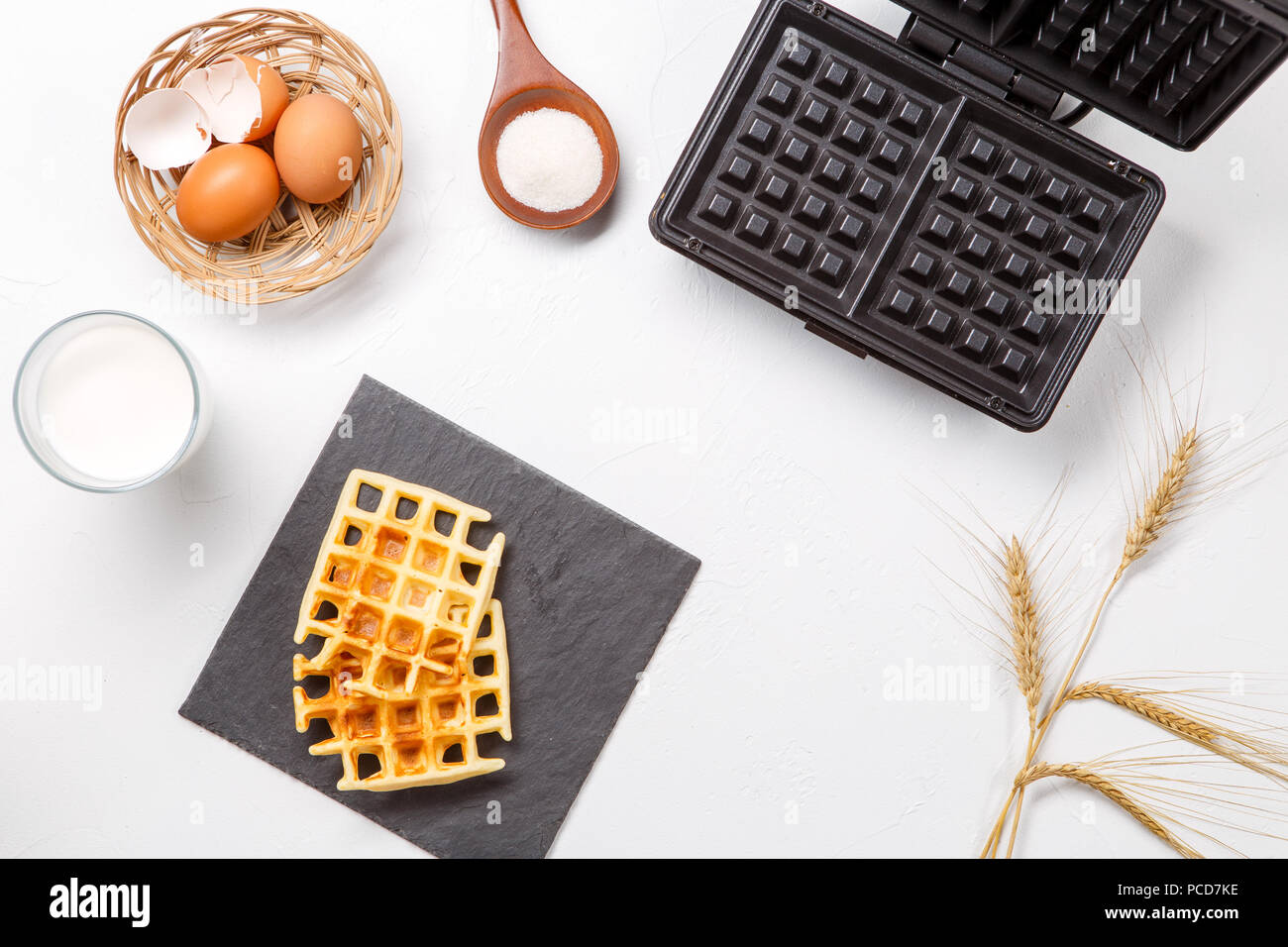 Photo on top of flour, eggs, waffle iron, spikes, fresh roasted waffles Stock Photo