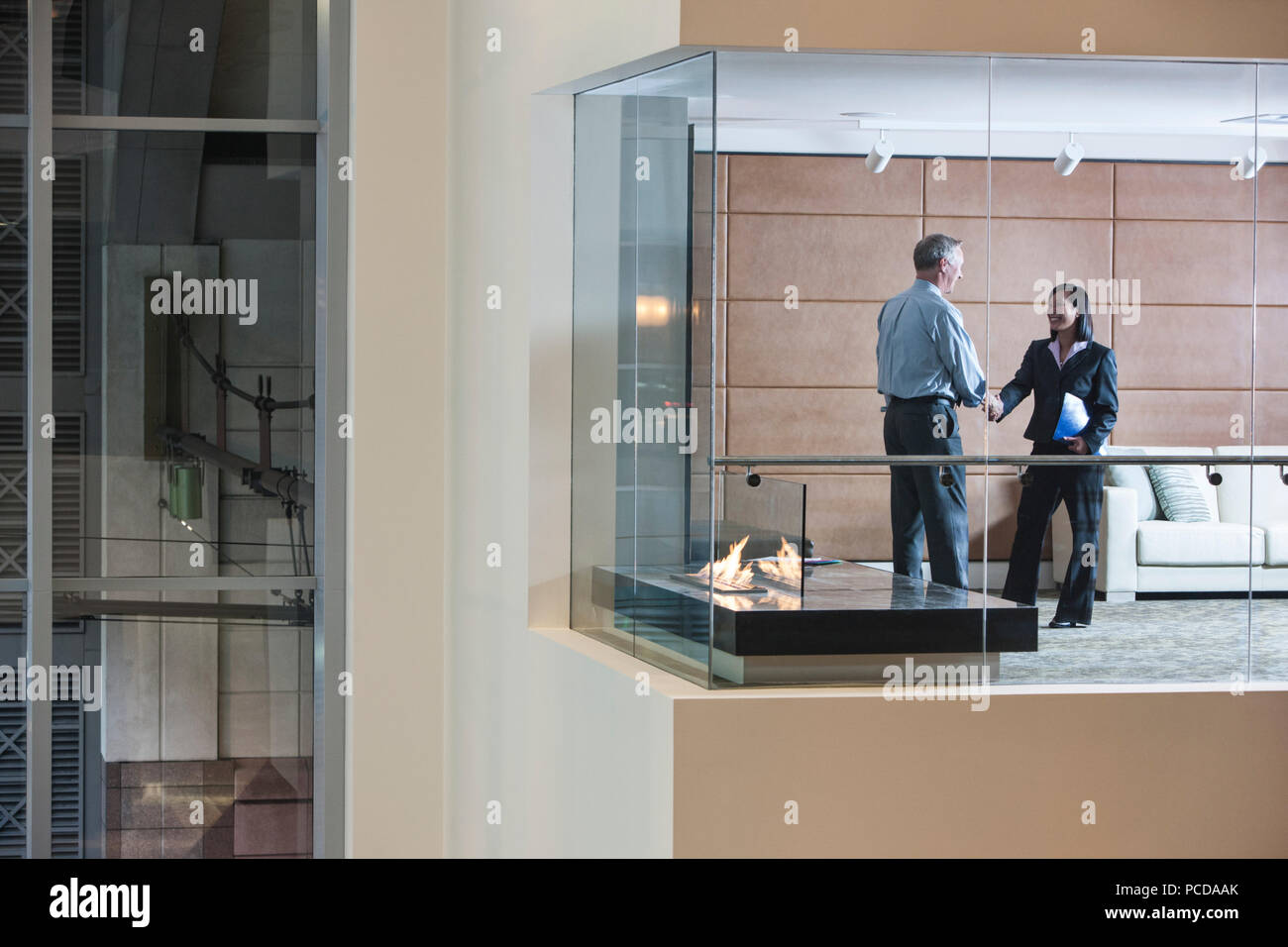 A Large Building Lobby View Looking Into An Office With Glass Walls Two Business People Talking Stock Photo Alamy