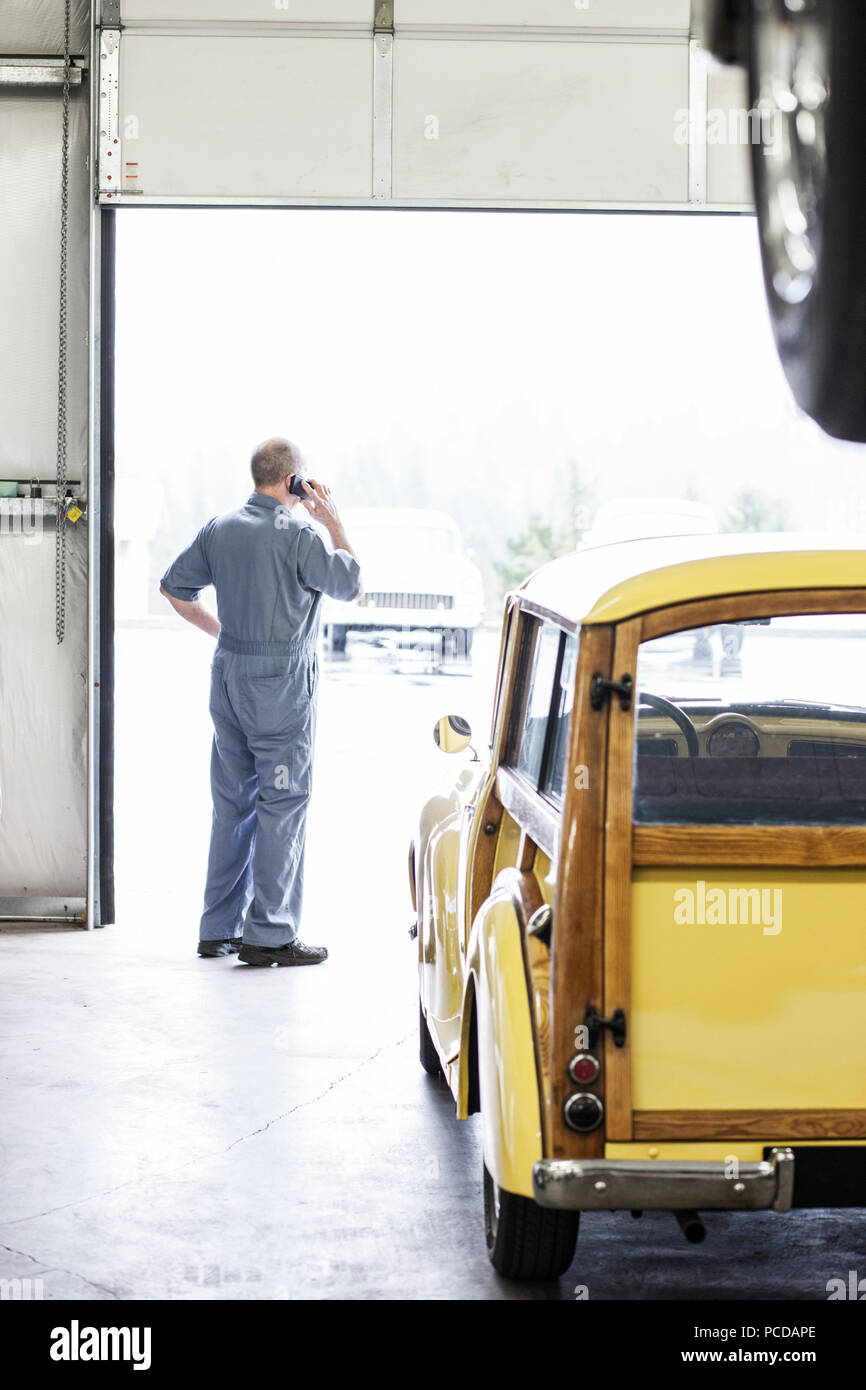 View from behind of an owner of a car repair shop on his cell phone. - Stock Image