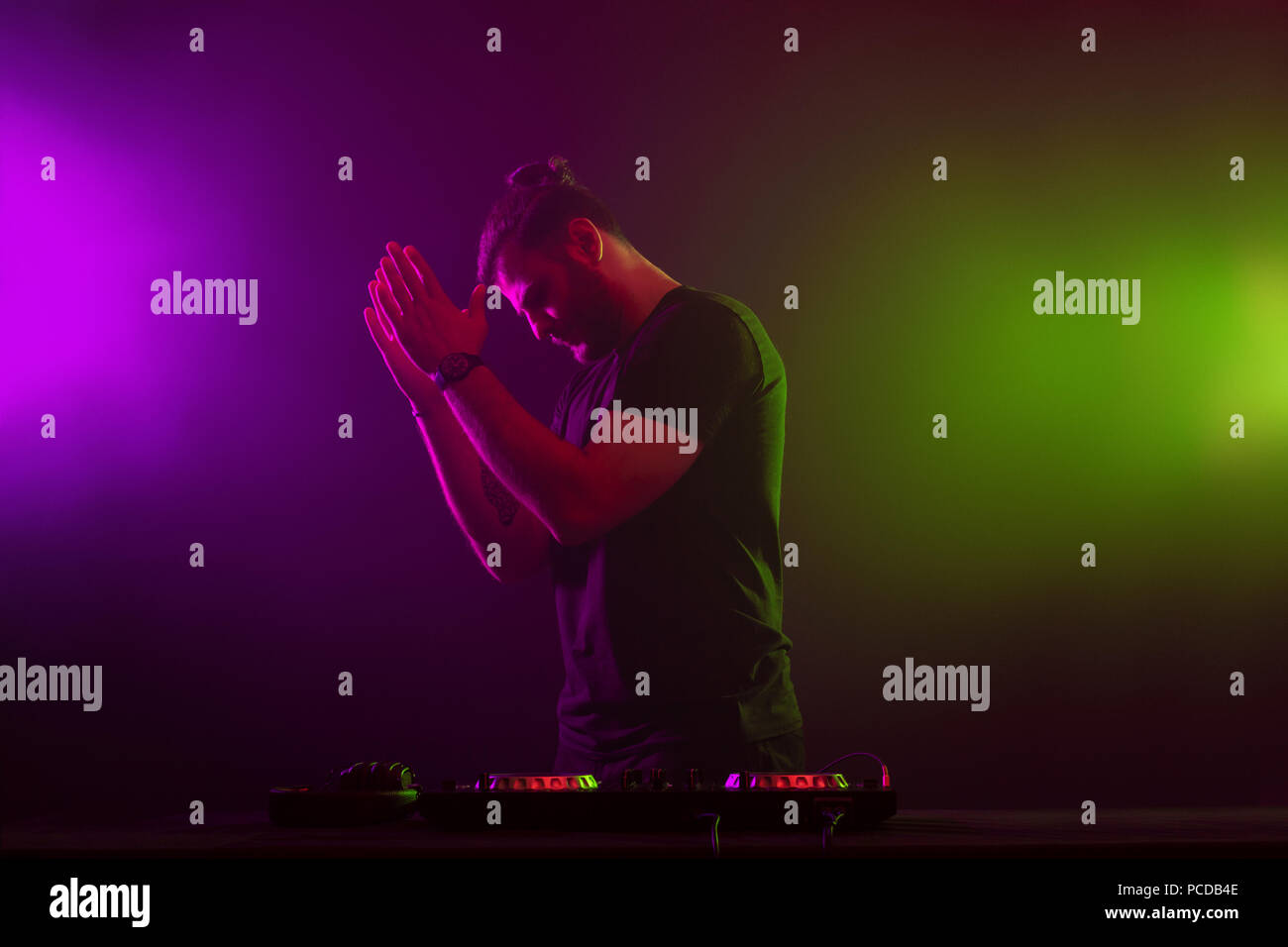 Handsome DJ in a black T-shirt at work mixing sound on her decks at a party or night club with colourful smoke light background - Stock Image