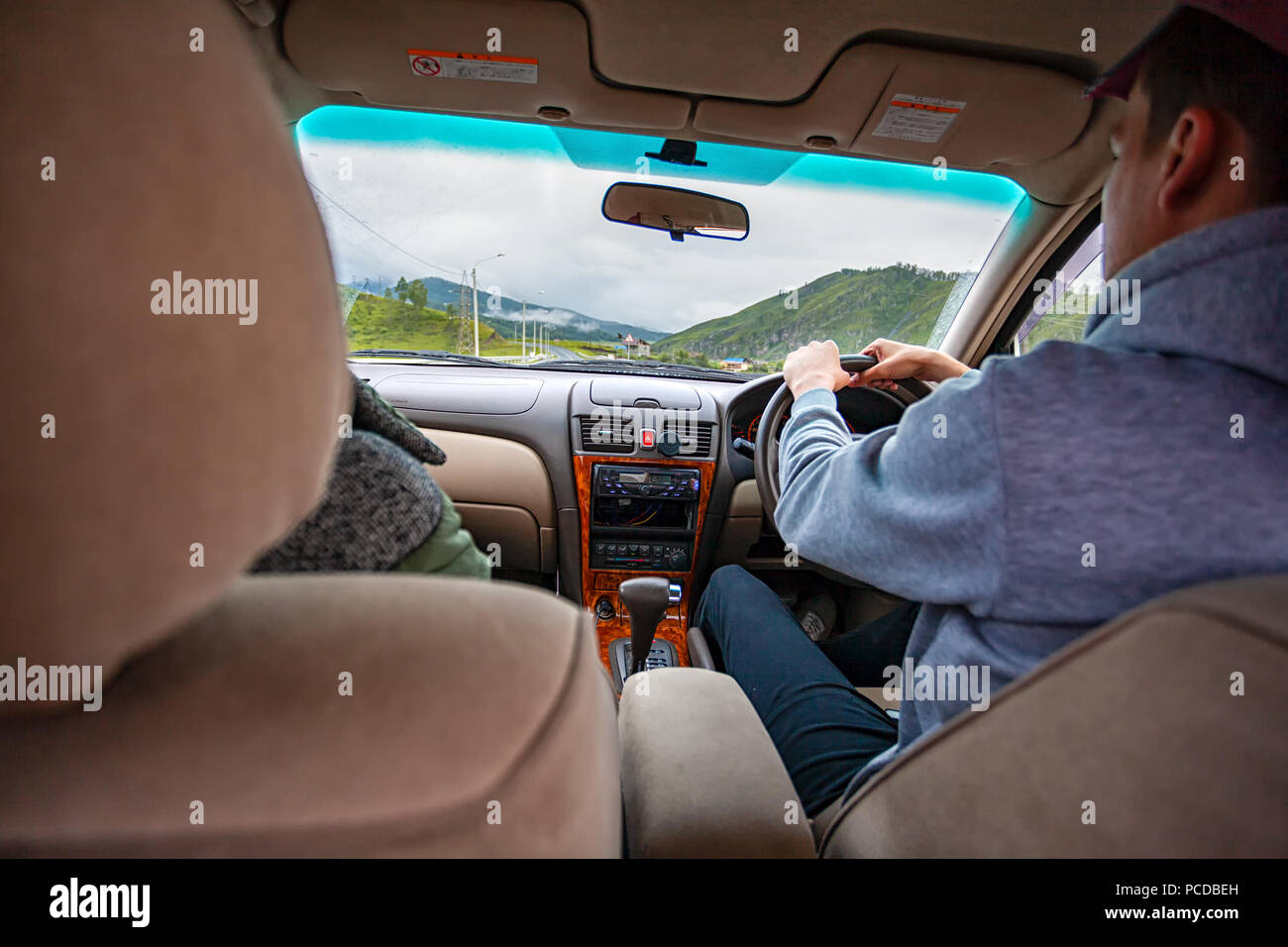 Close-up of a young couple of lovers riding a car on a trip to the mountains.Rear view portrait of man travels drive in a car for adventures. Lifestyl - Stock Image