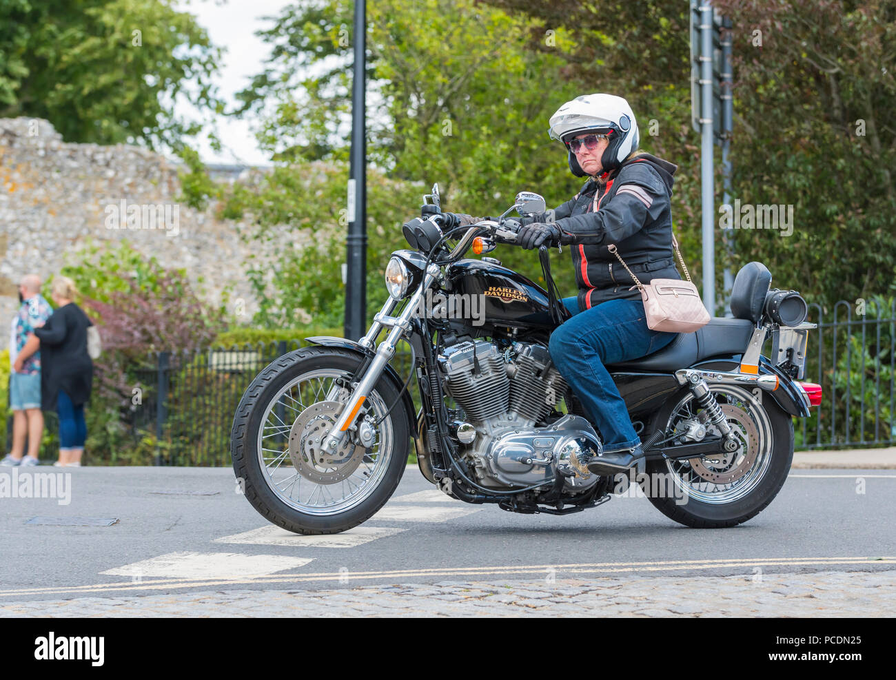 Woman riding a Harley Davidson 883 Sportster motorcycle with handbag over her shoulder in the UK. Female motorcyclist. - Stock Image