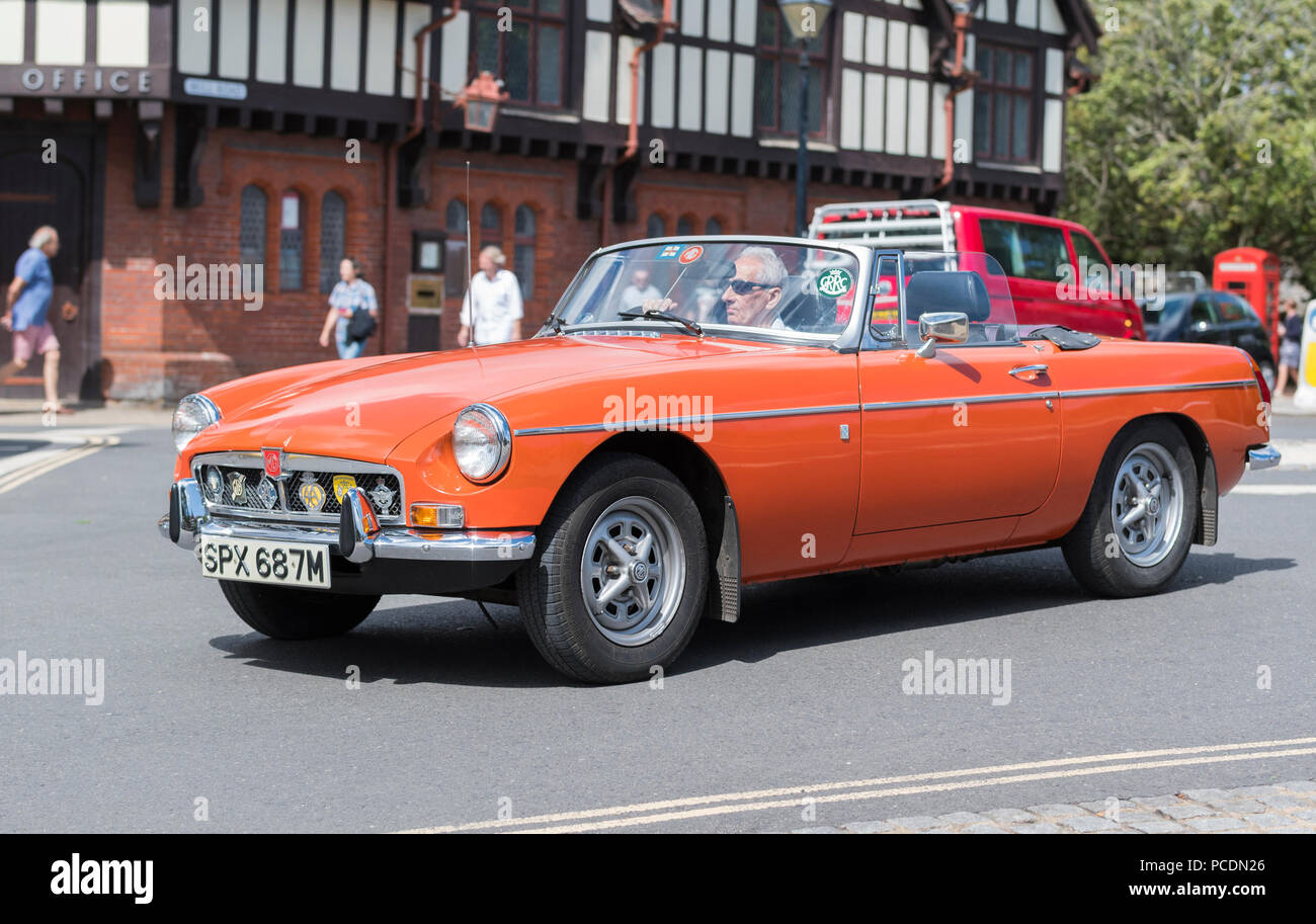 Orange BMC MG B (MGB) Coupe small 2 door convertible sports car from 1974 with the top down in Summer in West Sussex, England, UK. - Stock Image