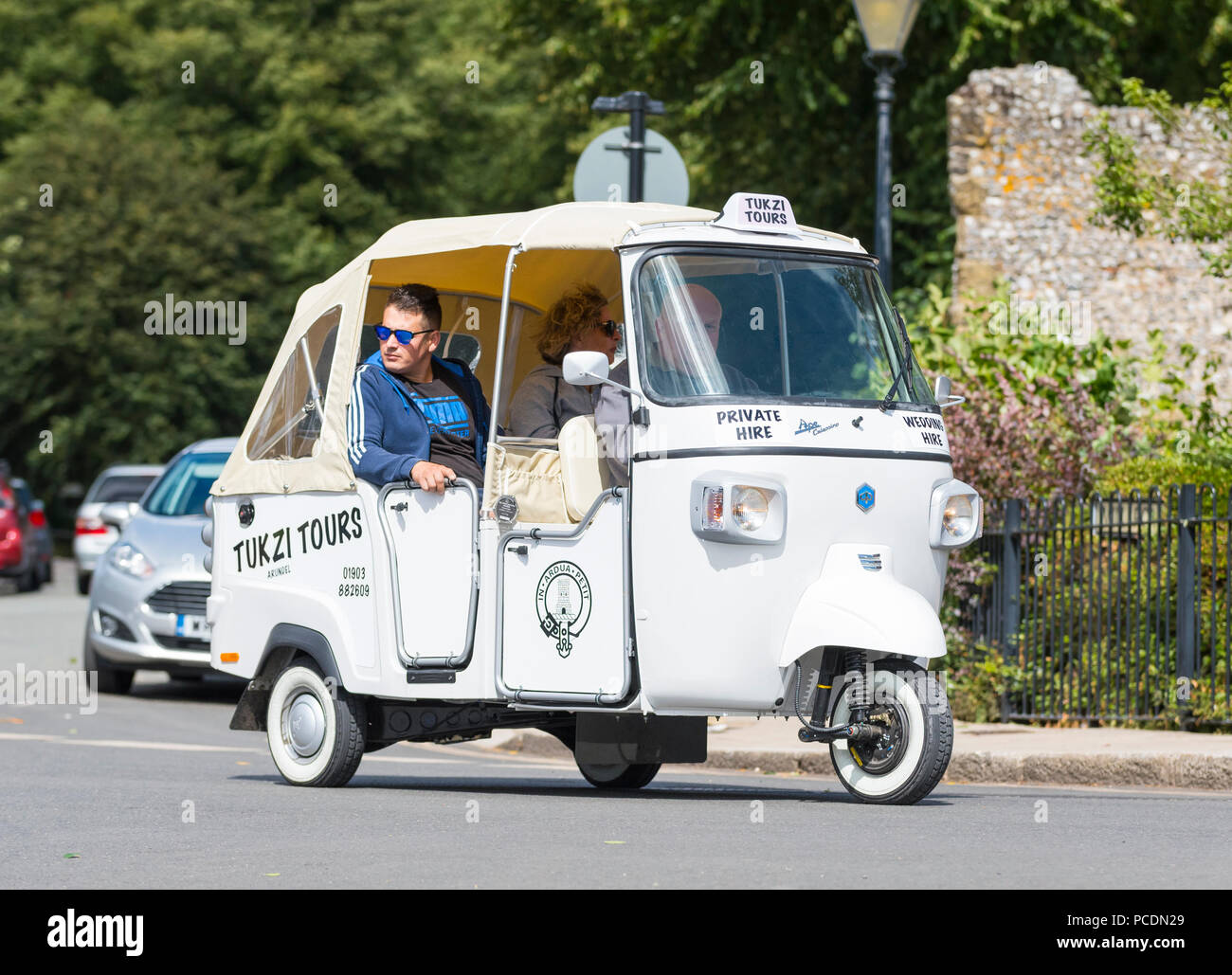 People having a town tour in a Piaggio Ape Calessino 3 wheeled cart (commonly known as a Tuk Tuk vehicle) from Tukzi Tours in Arundel, West Sussex, UK. - Stock Image