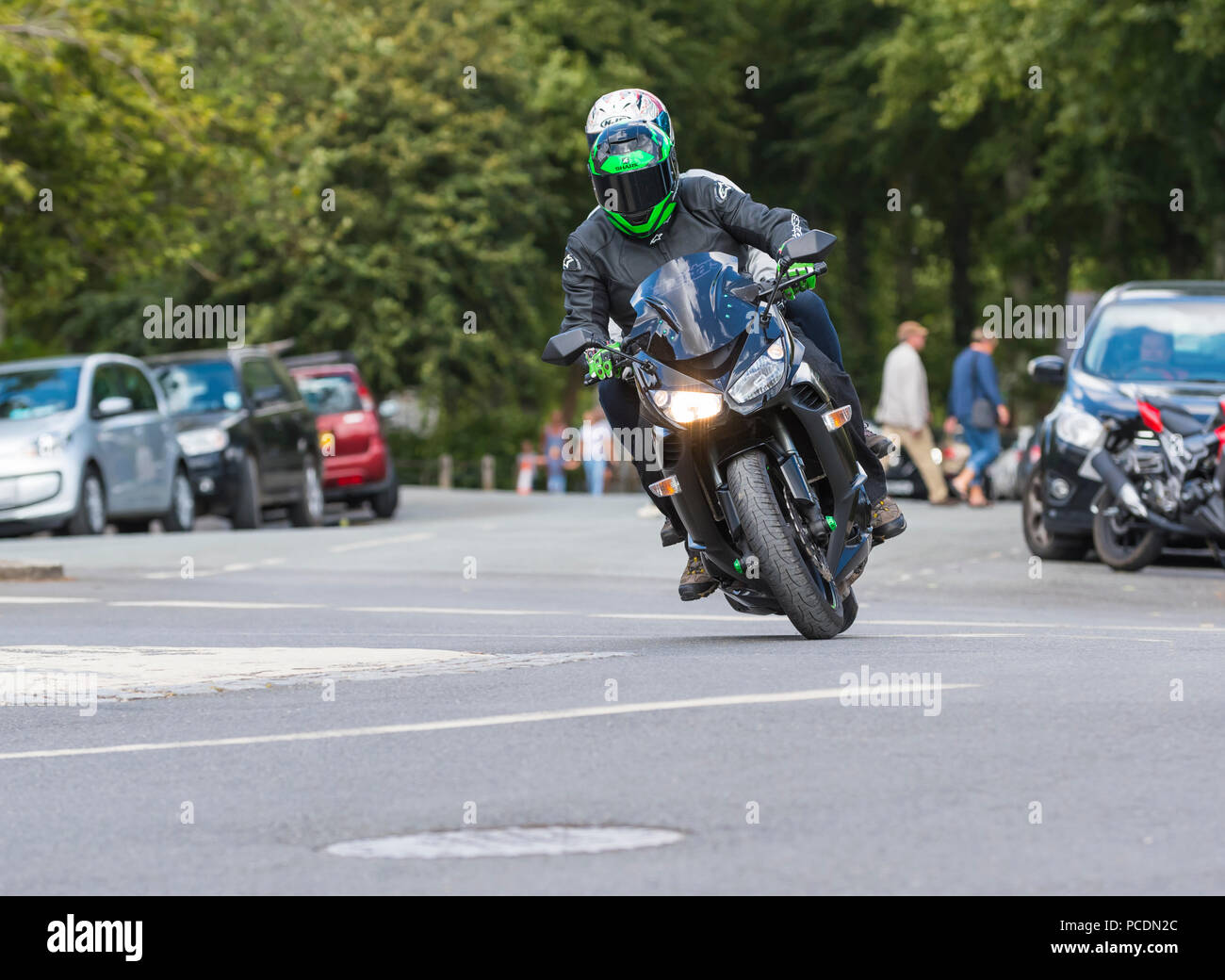 Person with pillion passenger riding on a Kawasaki Z1000SX motorcycle, leaning into a corner on a mini roundabout in West Sussex, England, UK. - Stock Image