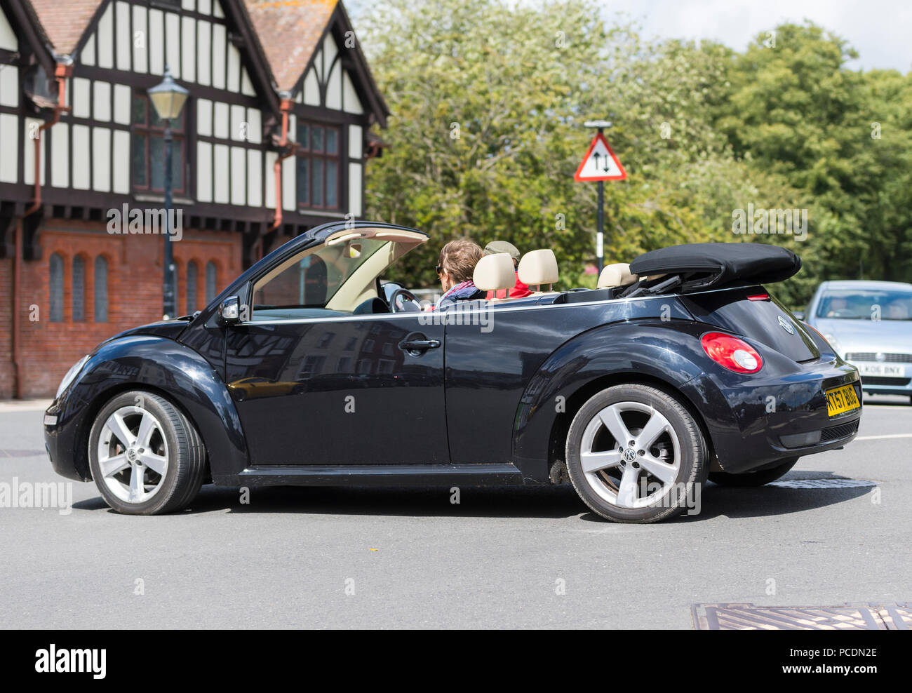 Black Volkswagen Beetle TDi convertible open top car from 2007 with the top down on a hot summer day in England, UK. - Stock Image