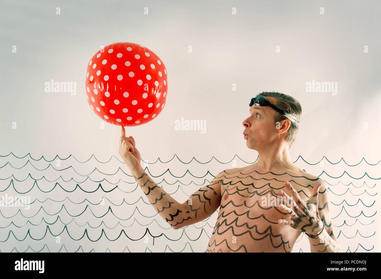 man,turning,beach ball - Stock Image