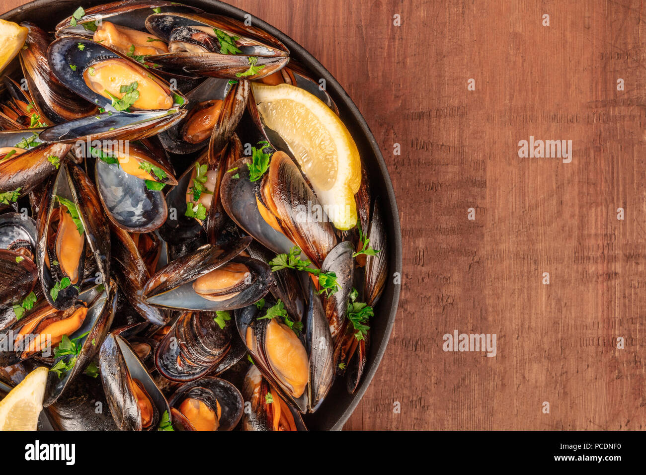 A full skillet of marinara mussels, shot from above on a dark rustic background with a place for text Stock Photo