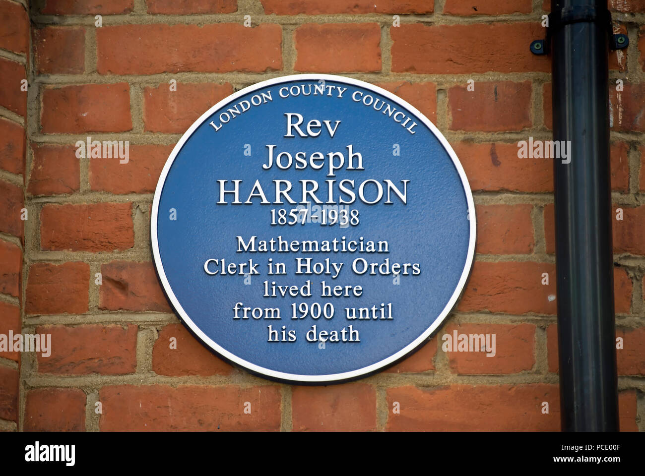 london county council blue plaque marking a home of the reverend joseph harrison, mathematician and clerk in holy orders, in ealing, london, england - Stock Image