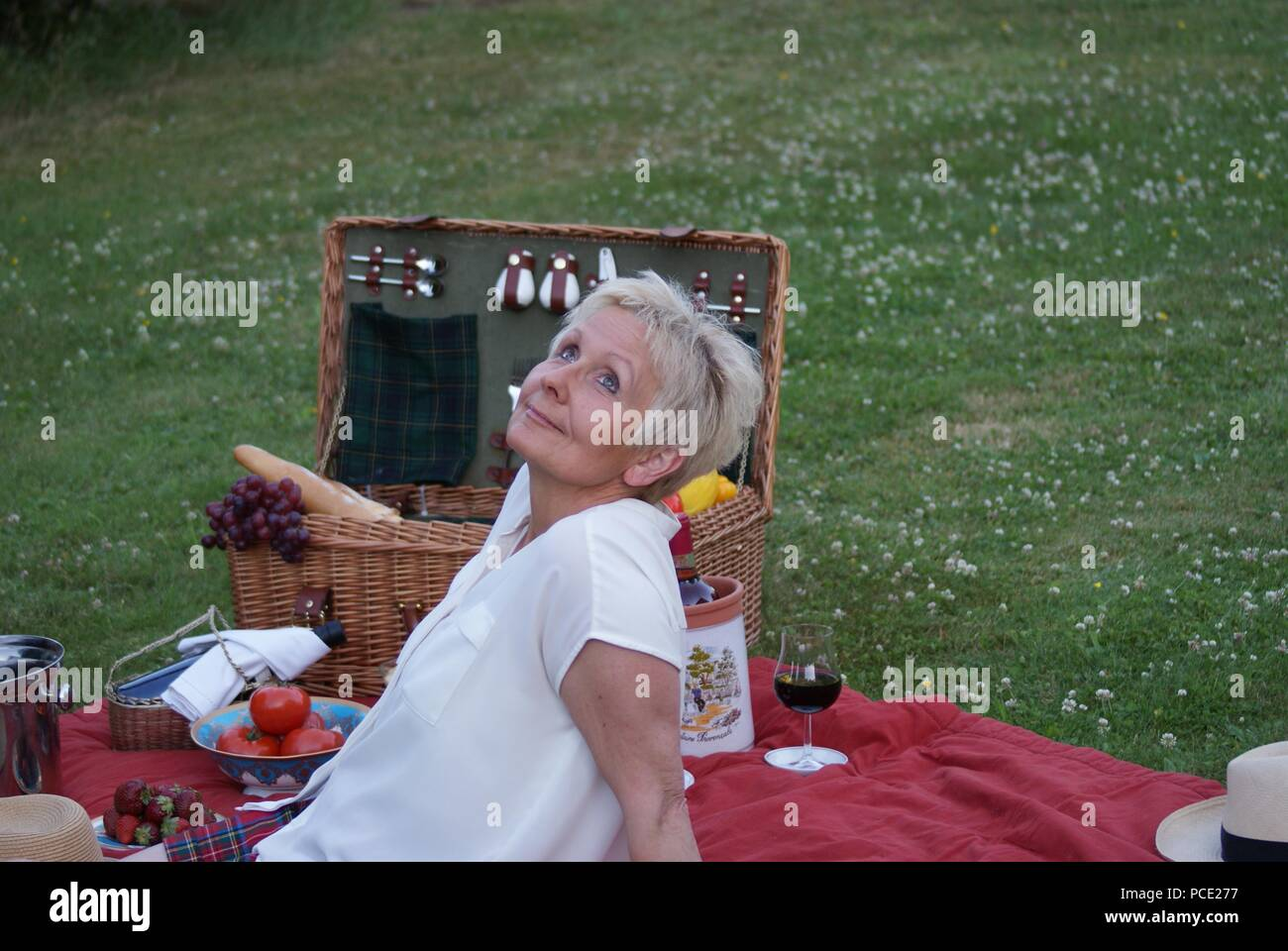 Picnic with fresh fruit, red wine and baguette, this blonde woman thinks fantastically Stock Photo