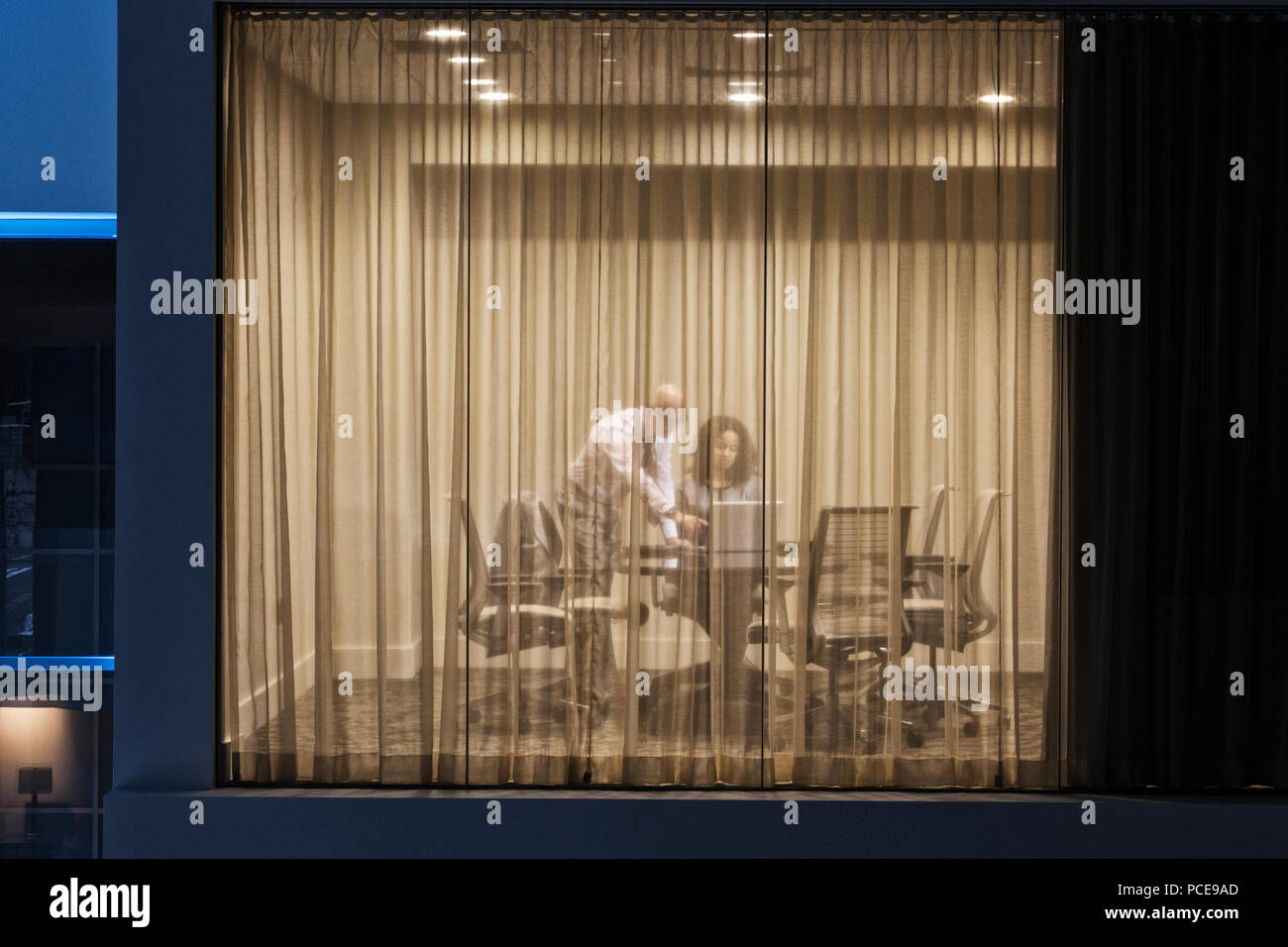 A night view looking into a conference room with two businesspeople working at conference table. - Stock Image
