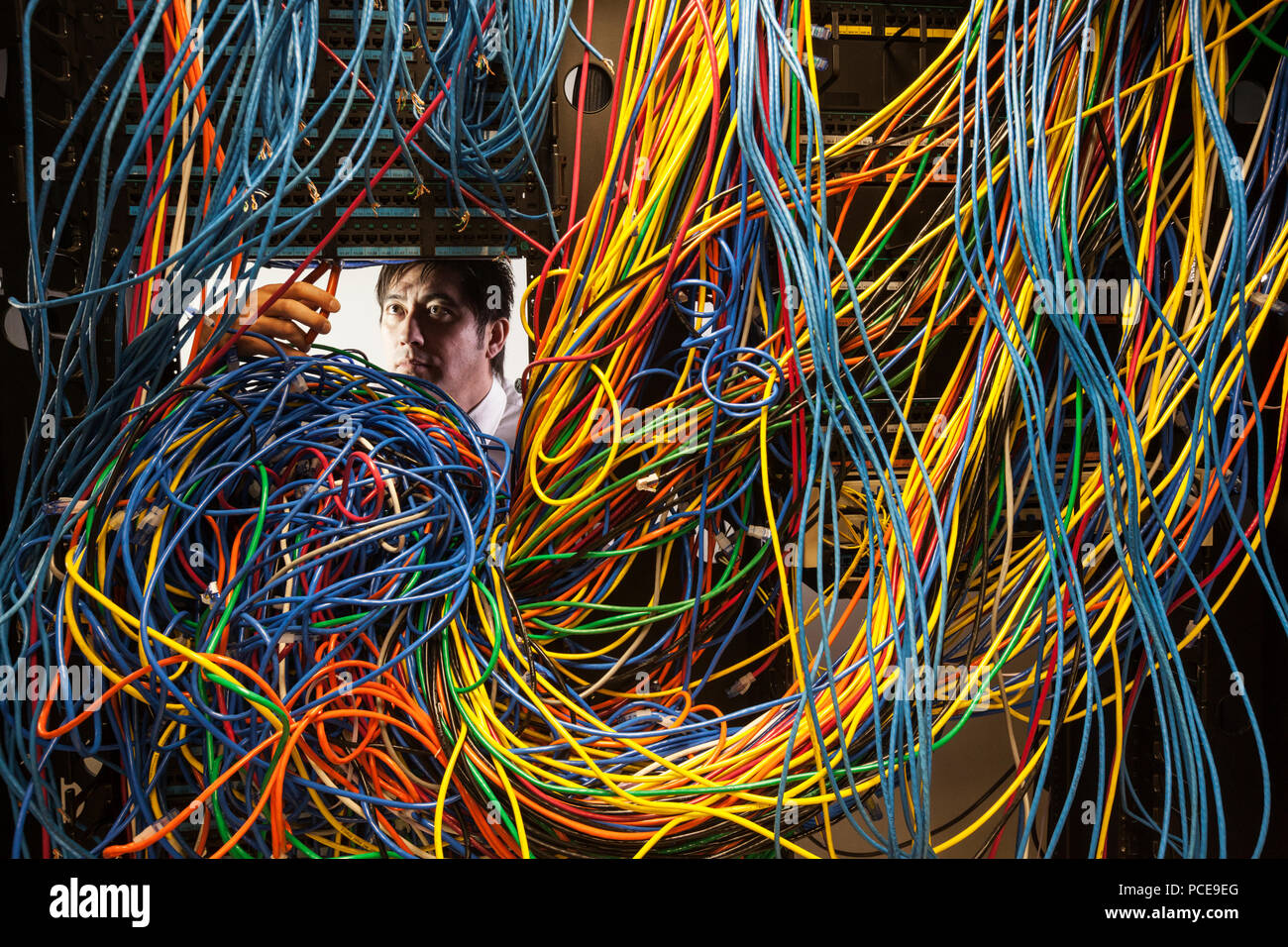 Asian Male Technician Working On A Tangled Mess Of Cat 5 Cables In Wiring Server Room