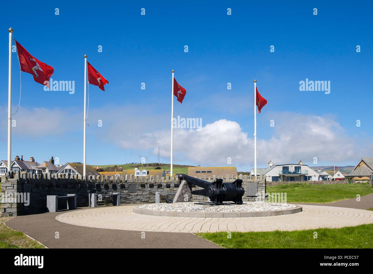 Manx flags flying at Dunkirk Memorial with anchor from Mona's Queen III sunk during Operation Dynamo. Kallow Point, Port St Mary, Isle of Man - Stock Image