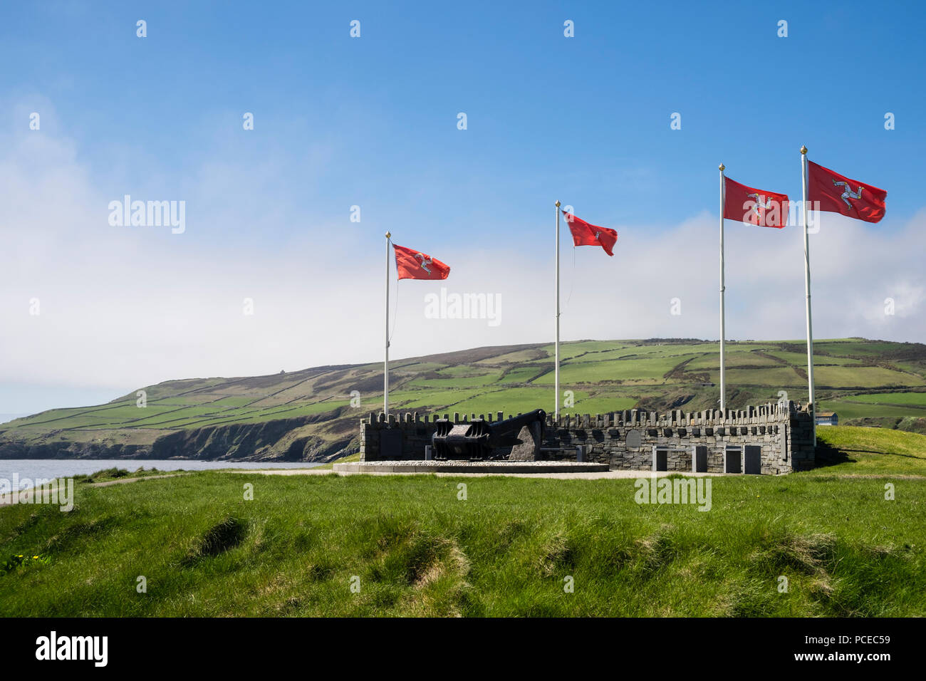 Manx flags flying at Dunkirk Memorial on coast at Kallow Point, Port St Mary, Isle of Man, British Isles - Stock Image