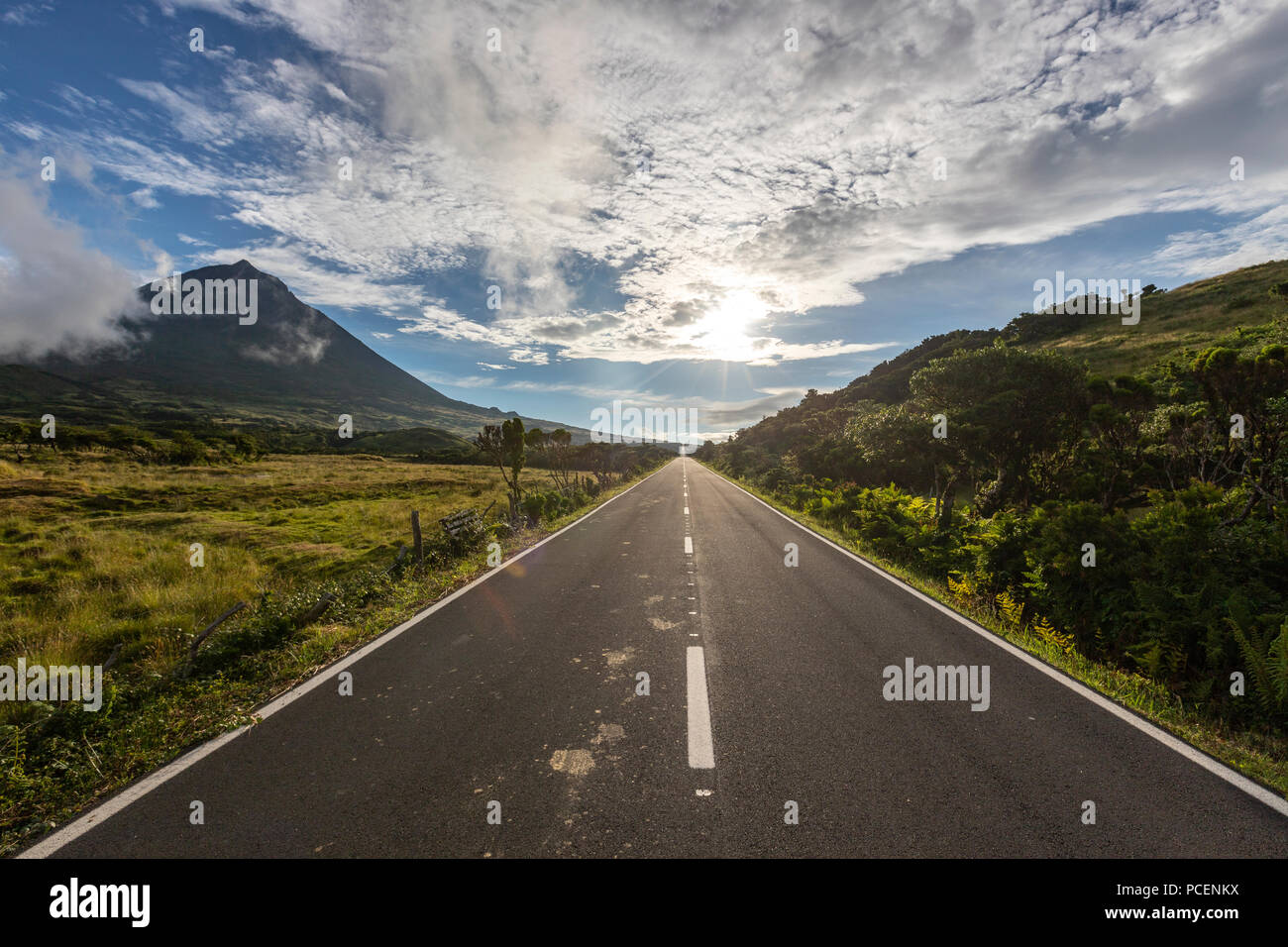 Straight EN3 longitudinal road northeast of Mount Pico and the silhouette of the Mount Pico along , Pico island, Azores, Portugal - Stock Image