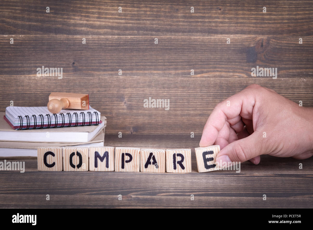 compare. wooden letters on the office desk - Stock Image