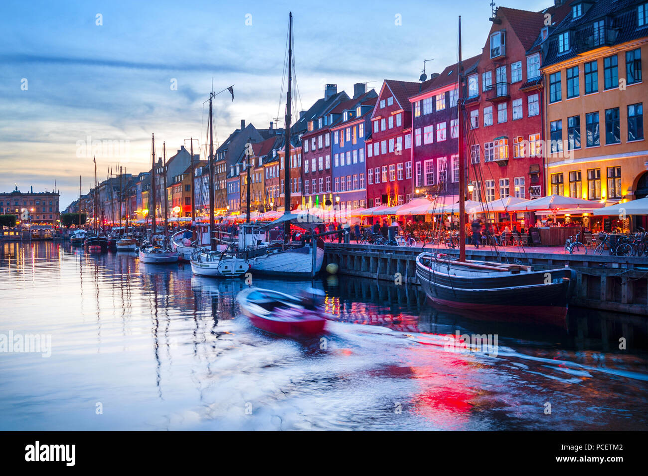 Evening scene with boats moored by illuminated Nyhavn harbor embankment, Copenhagen, Denmark - Stock Image