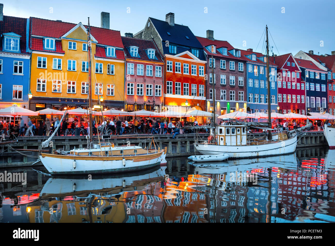 Sailboats moored by Nyhavn promenade illuminated at the evening, Copenhagen old town cityscape, Denmark - Stock Image