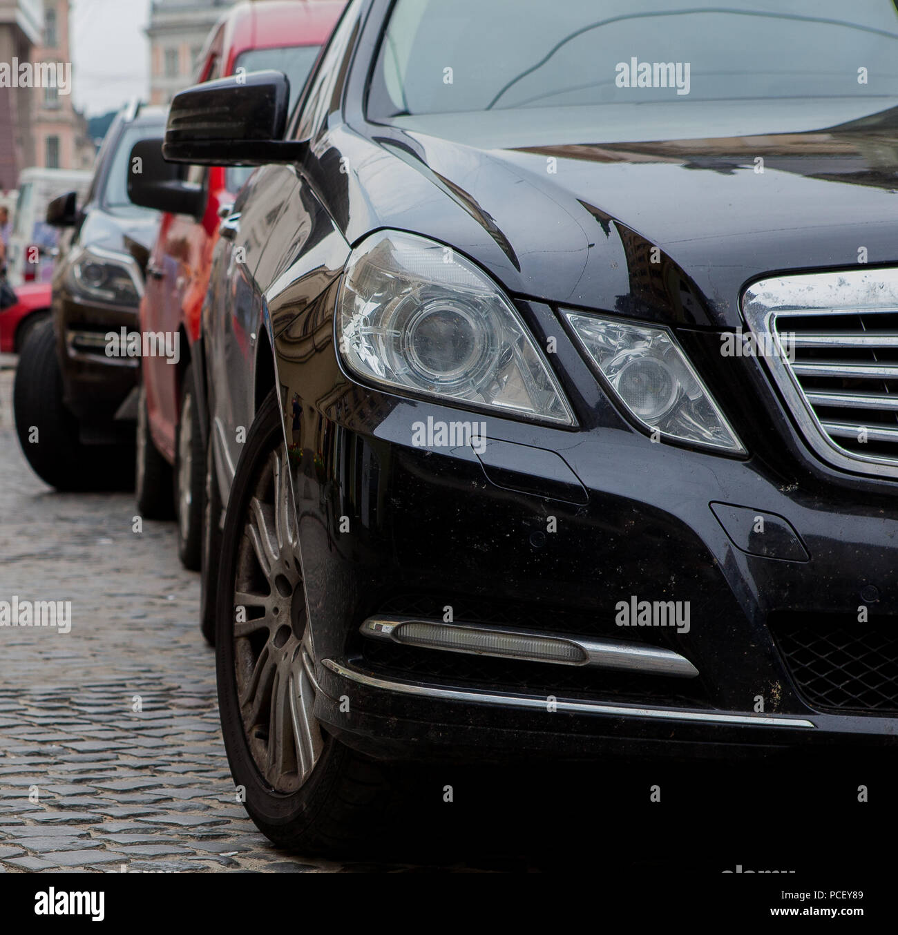 Close Up Headlight Of Black Modern Car With Other Cars On Background