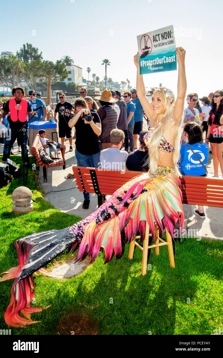 A young female demonstrator in a mermaid costume joins a