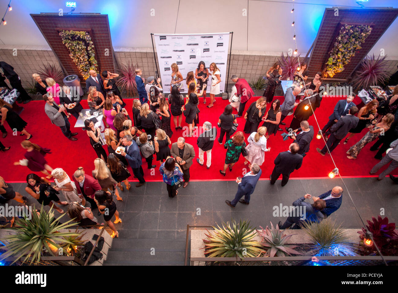 Cast members mix with invited guests at a party publicizing the reality TV show 'Real Estate Wars' in Laguna Beach, CA. In center is a background for people posing for photographers.  (Photo by Spencer Grant) - Stock Image