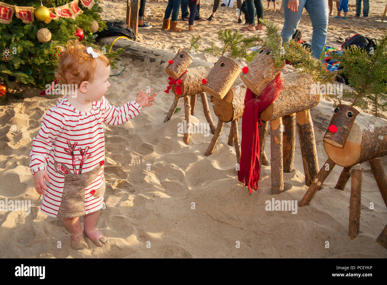 Wearing a Rudolph the Red-Nose Reindeer dress, a 16-month-old girl is bemused by a row of wooden model Rudolphs in Laguna Beach, CA, one them decked out in a maroon scarf..  (Photo by Spencer Grant) - Stock Image