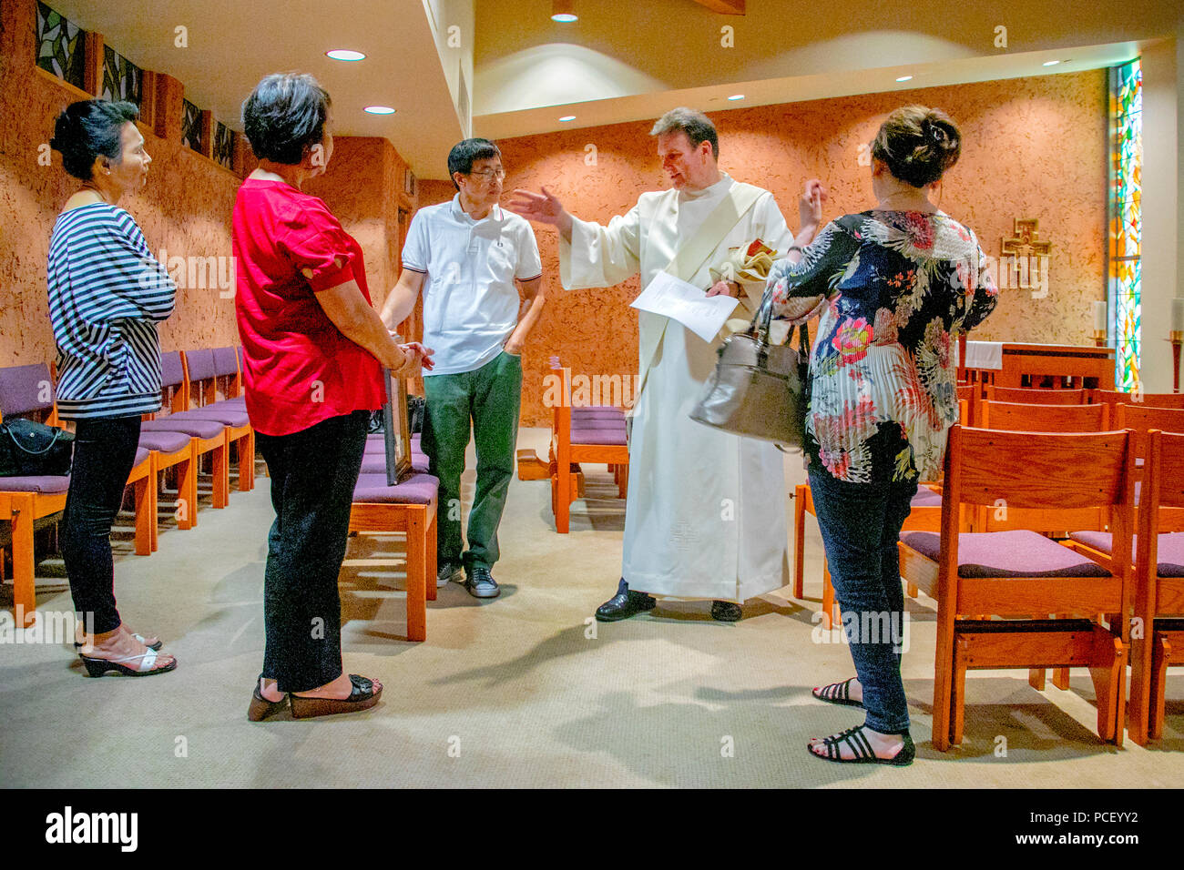 A robed deacon chats with parishioners after conducting a Divine Mercy With Benediction service to a multiracial congregation in the chapel of a Laguna Niguel, CA, Catholic church. - Stock Image