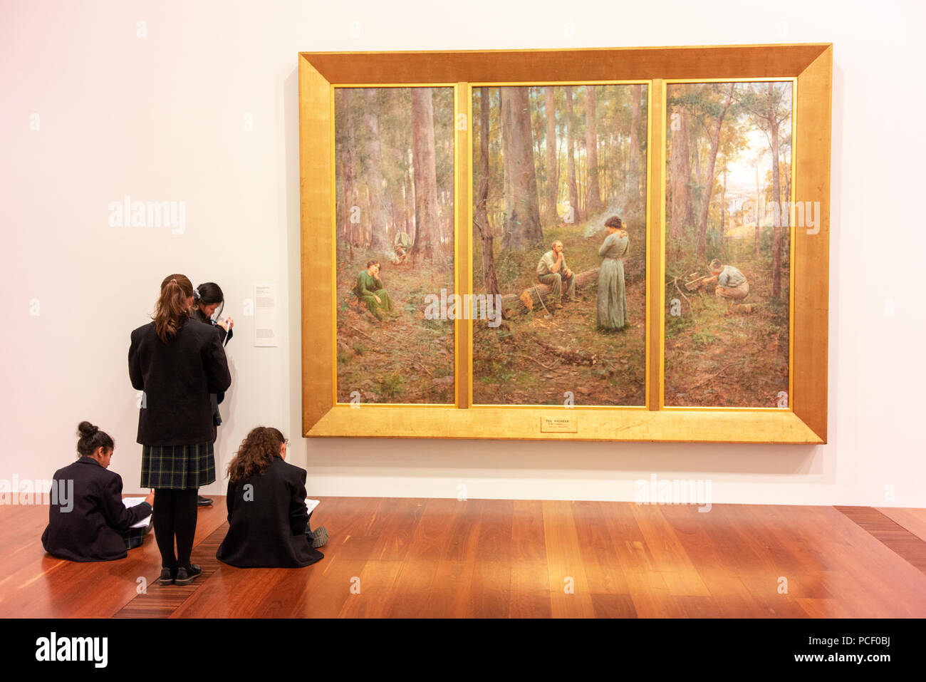 Students studying art works at the Ian Potter Centre, part of the National Gallery of Victoria which holds collections of Australian and other art. - Stock Image