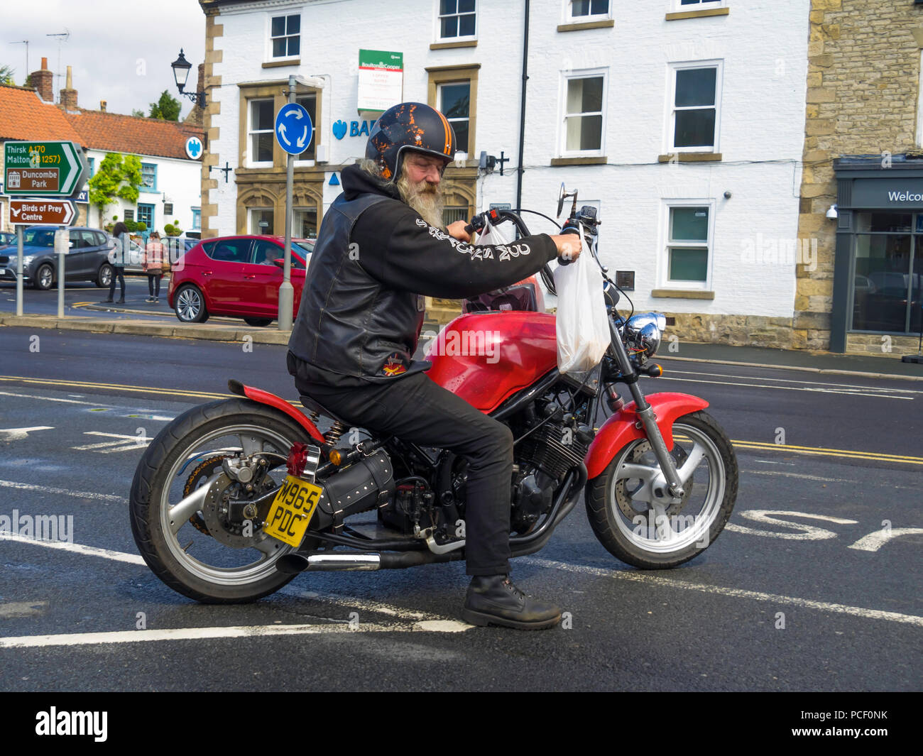 Elderly grey bearded motorcyclist on the custom built motorcycle he built himself, wafting to pull out into traffic Stock Photo