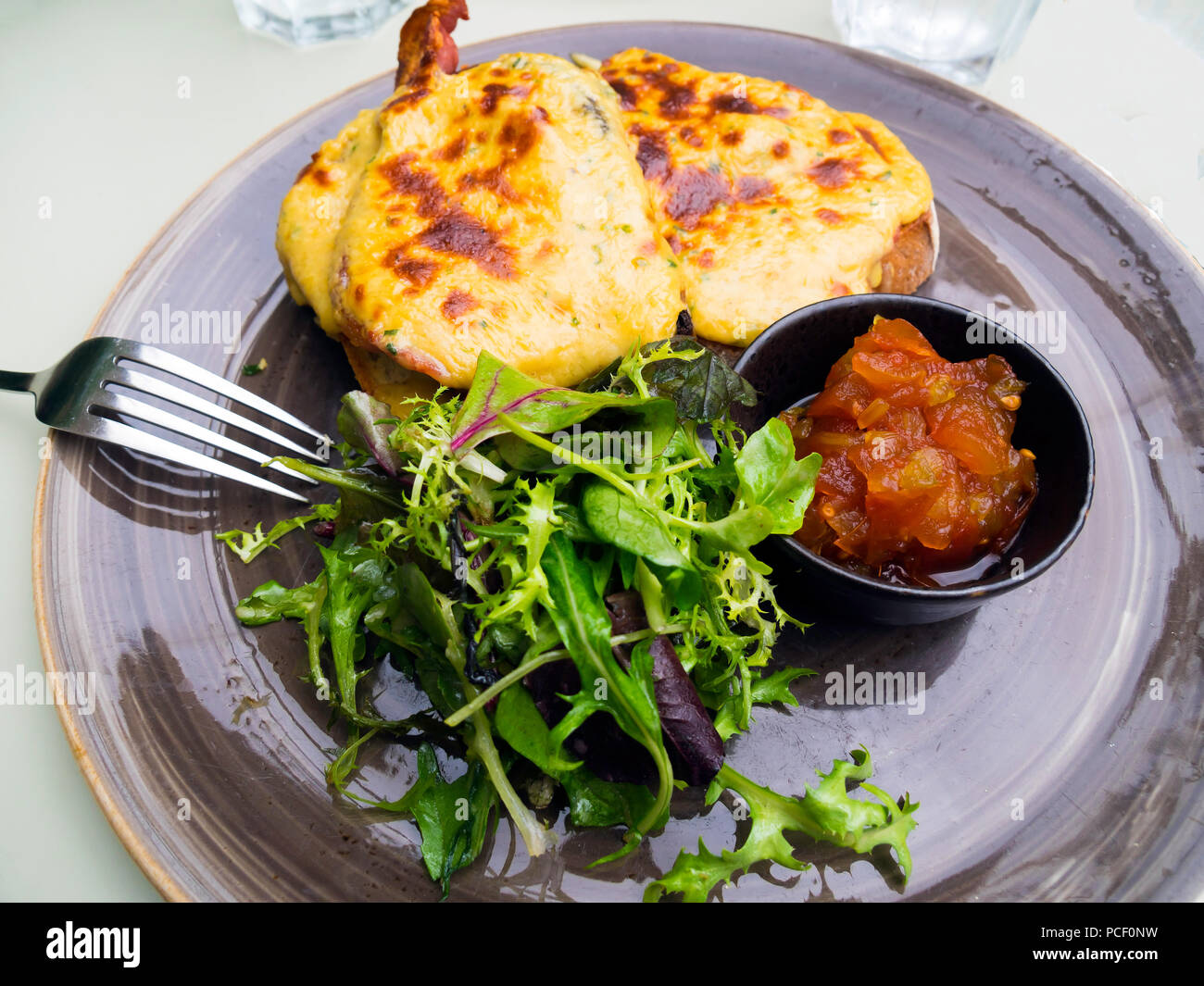 Toasted Yorkshire Rarebit with grilled bacon salad and tomato and ginger relish Stock Photo