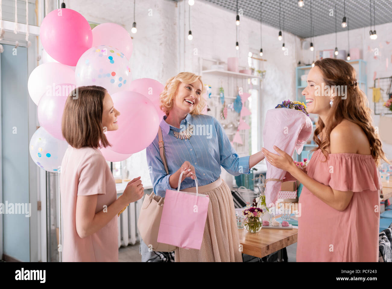 Two friends making surprise for their anticipating colleague - Stock Image