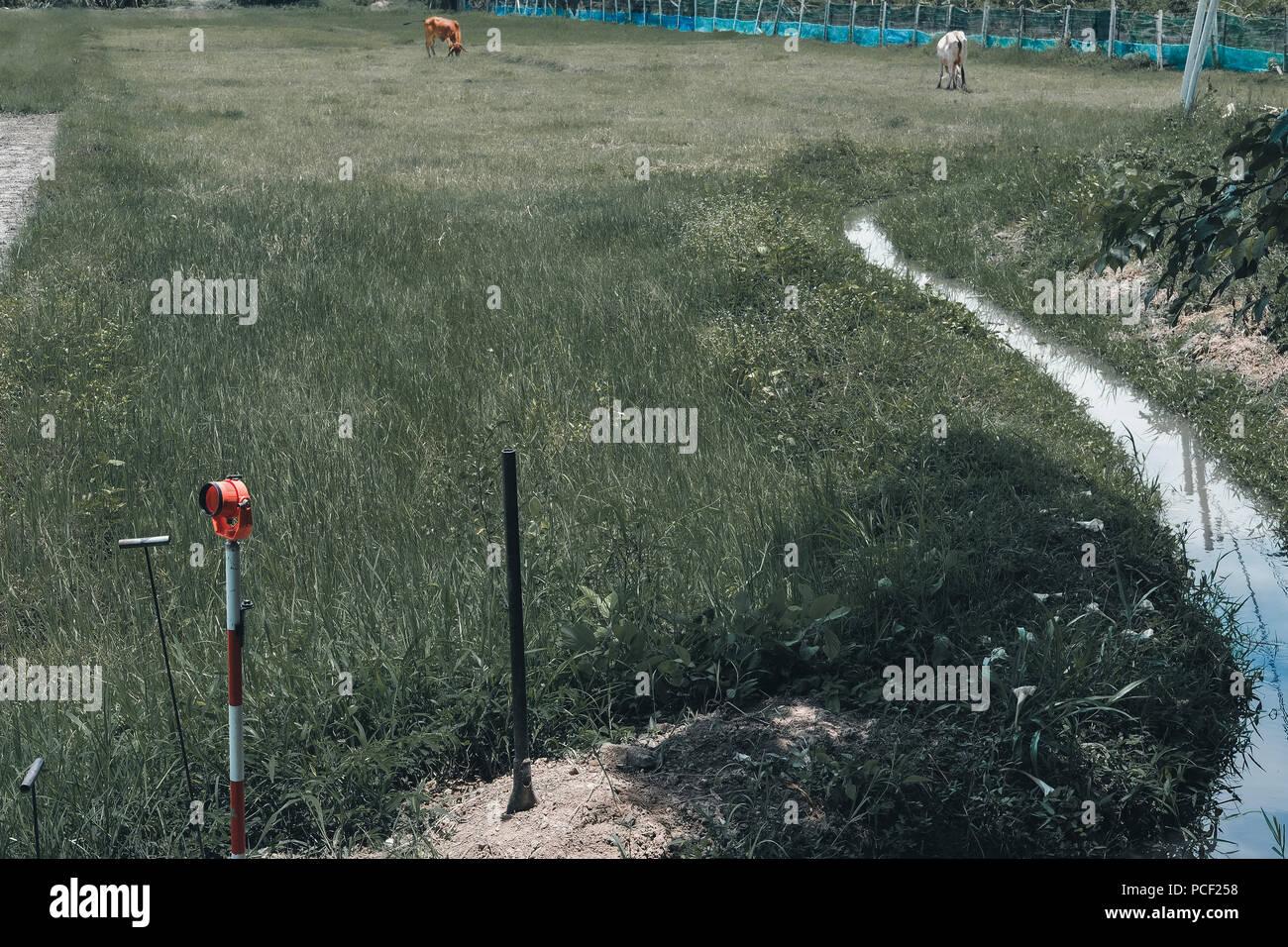 land surveyor using pole for measuring ground control point