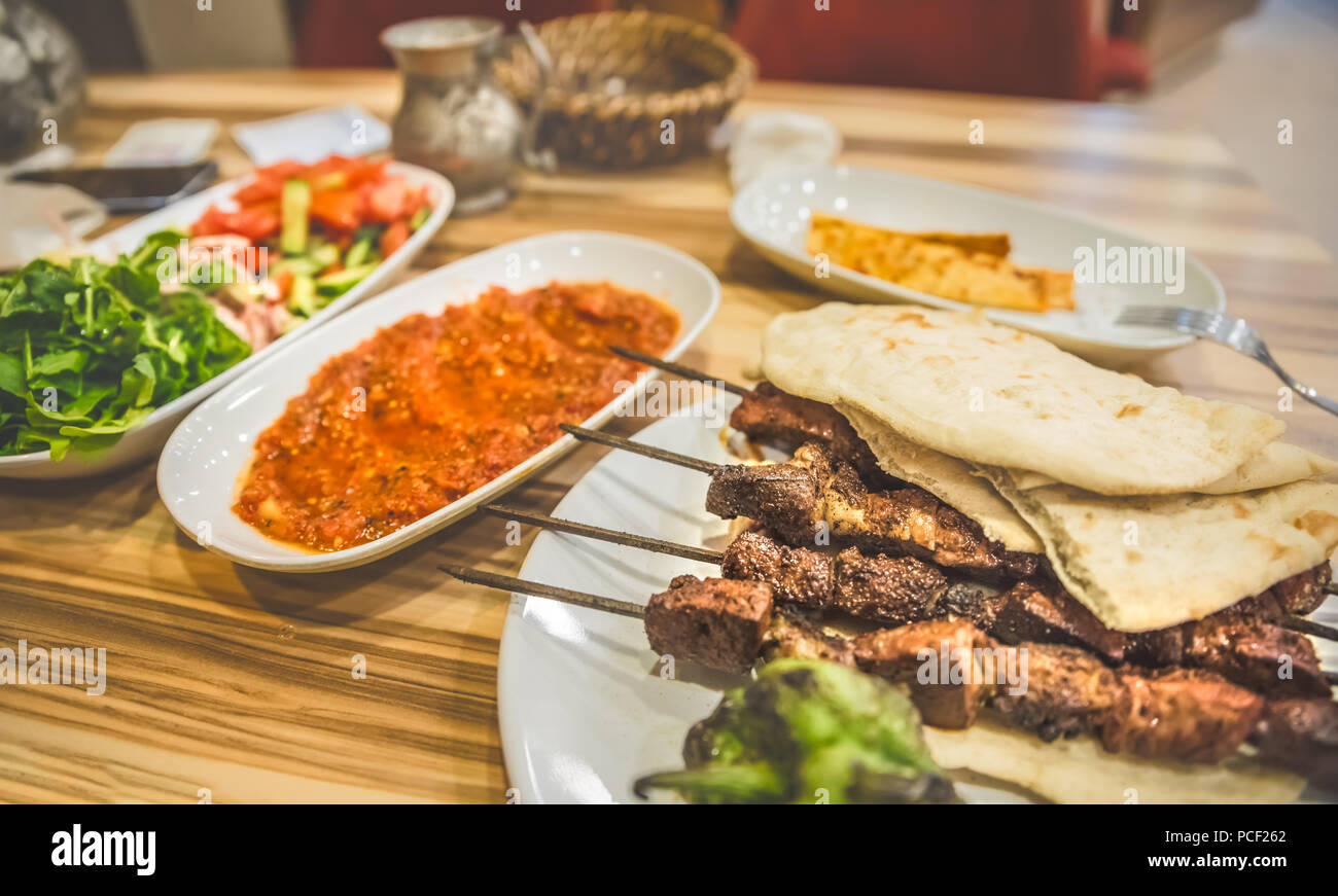 Close up detailed view of grilled delicious Turkish liver shish kebab served on a white plate with sliced lavash,salad and ayran. - Stock Image