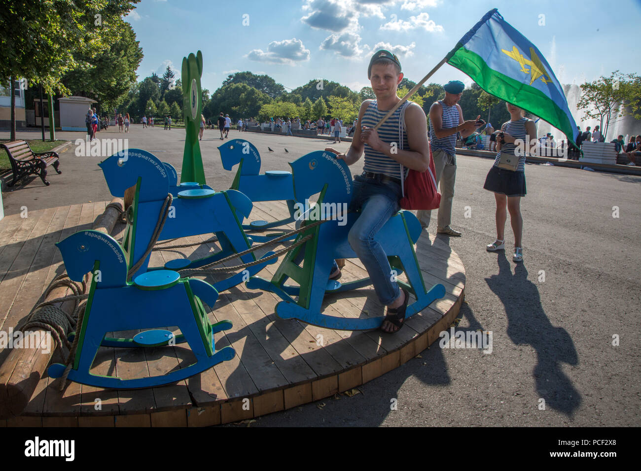 Paratrooper in a blue beret riding a children's horse in Gorky Park durign celebration of the airborne troops day in Moscow, Russia. - Stock Image